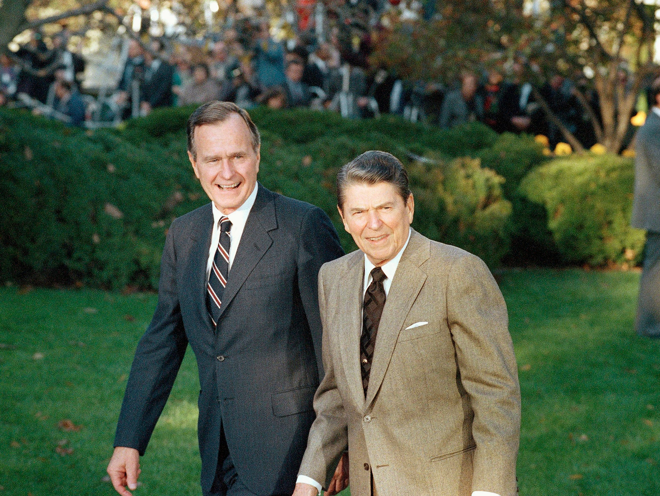 Pres. Ronald Reagan greets President-elect George H. W. Bush, left, upon his arrival to the White House, Wednesday, Nov. 10, 1988, Washington, D.C. (AP Photo/Charles Tasnadi)