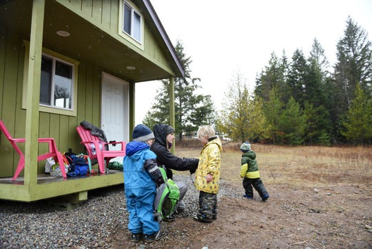 In this Wednesday, Oct. 31, 2018 photo, Teacher Kayla Nickells removes wet hats and gloves from students after a hike at Foxtail Förskola at Earthstar Farms in Whitefish, Mont. Foxtail Förskola is a Scandinavian-inspired forest school where nature is the classroom. Children ages 3-6 spend nearly all of the school day outdoors learning social and emotional readiness through free play and nature-based activities on a 35-acre organic farm. (Casey Kreider/The Daily Inter Lake via AP)