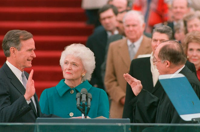 President George H.W. Bush raises his right hand on Jan. 19, 1989, as he is sworn into office as the 41st president of the United States by Chief Justice William Rehnquist as first lady Barbara Bush holds the Bible.