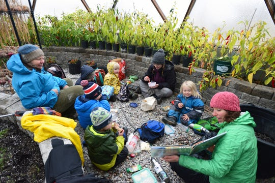 In this Wednesday, Oct. 31, 2018 photo, Teacher-assistant Amy Kortko reads a children's book to the group during a break for lunch and story time inside a greenhouse at Foxtail Förskola at Earthstar Farms in Whitefish, Mont. Foxtail Förskola is a Scandinavian-inspired forest school where nature is the classroom. Children ages 3-6 spend nearly all of the school day outdoors learning social and emotional readiness through free play and nature-based activities on a 35-acre organic farm.  (Casey Kreider/The Daily Inter Lake via AP)