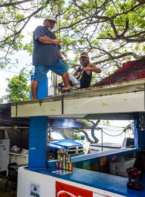 Merizo Mayor's Office employees, Joseph Tainatongo, left, and John Barcinas, work atop one of the vendor pavillions during the annual Malesso Fiestan Tasi on Saturday, Dec. 1, 2018 at the Malesso Veteran Sons & Daughters Pier Park. The village festival is slated to continue on Sunday, Dec. 2, with plans of a spearfishing competition, personal watercraft racing, live entertainment and an evening fireworks show being held.
