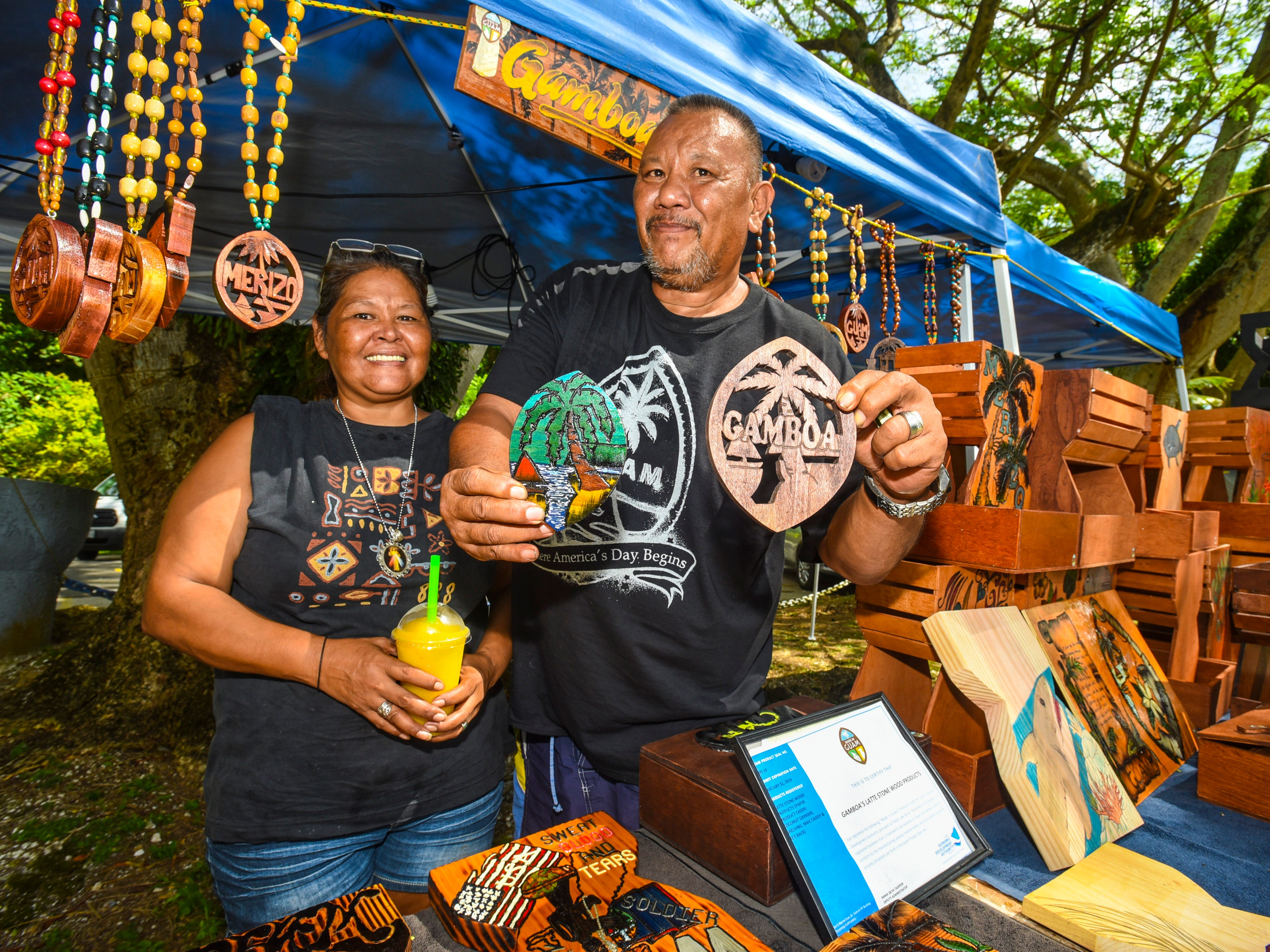 Couple, Francisco Gamboa Jr., right, and Dianne Palomo, of Gamboa's Latte Stone Wood Products, display and stand amongst some of their handicrafts being sold at their vendor stall during the annual Malesso Fiestan Tasi on Saturday, Dec. 1, 2018 at the Malesso Veteran Sons & Daughters Pier Park. The village festival is slated to continue on Sunday, Dec. 2, with plans of a spearfishing competition, personal watercraft racing, live entertainment and an evening fireworks show being held.