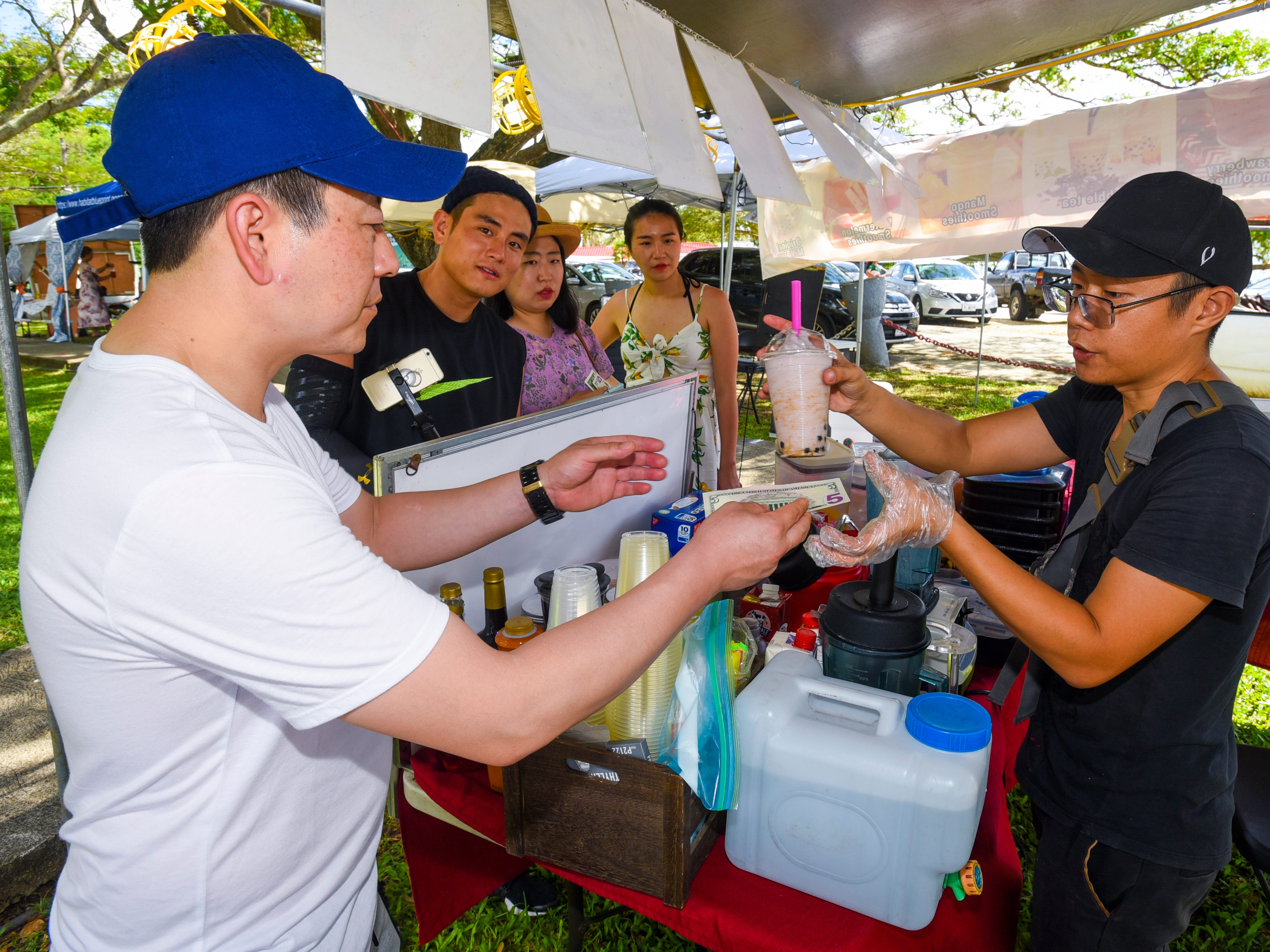 Yang Li, right, of the Momo's Cafe vendor stall, serves a chillin' taro smoothie to a customer during the annual Malesso Fiestan Tasi on Saturday, Dec. 1, 2018 at the Malesso Veteran Sons & Daughters Pier Park. The village festival is slated to continue on Sunday, Dec. 2, with plans of a spearfishing competition, personal watercraft racing, live entertainment and an evening fireworks show being held.
