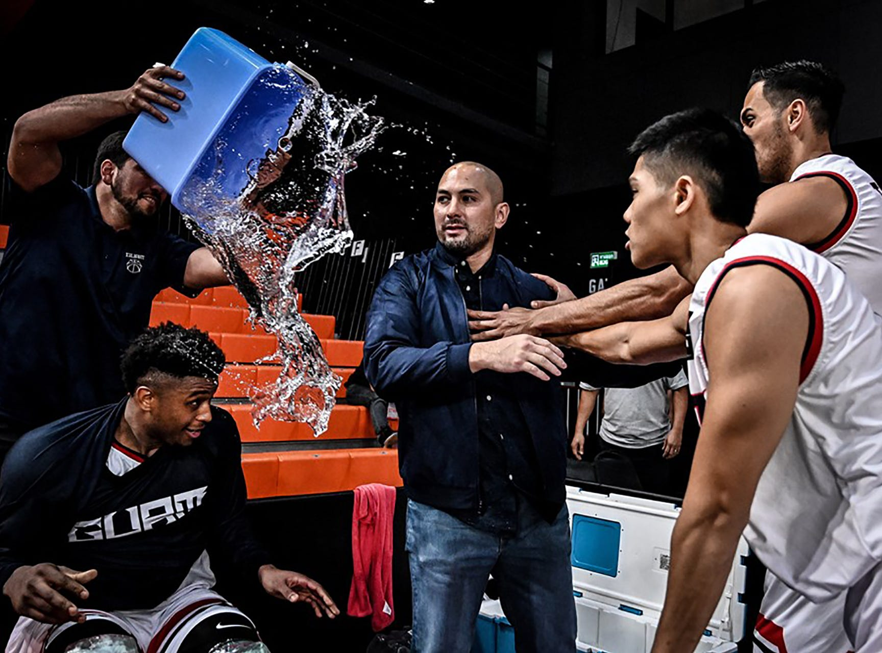 Team Guam head coach E.J. Calvo  realizes too late what's coming - a victory bucket of cold water, courtesy of team manager Seve Susuico.