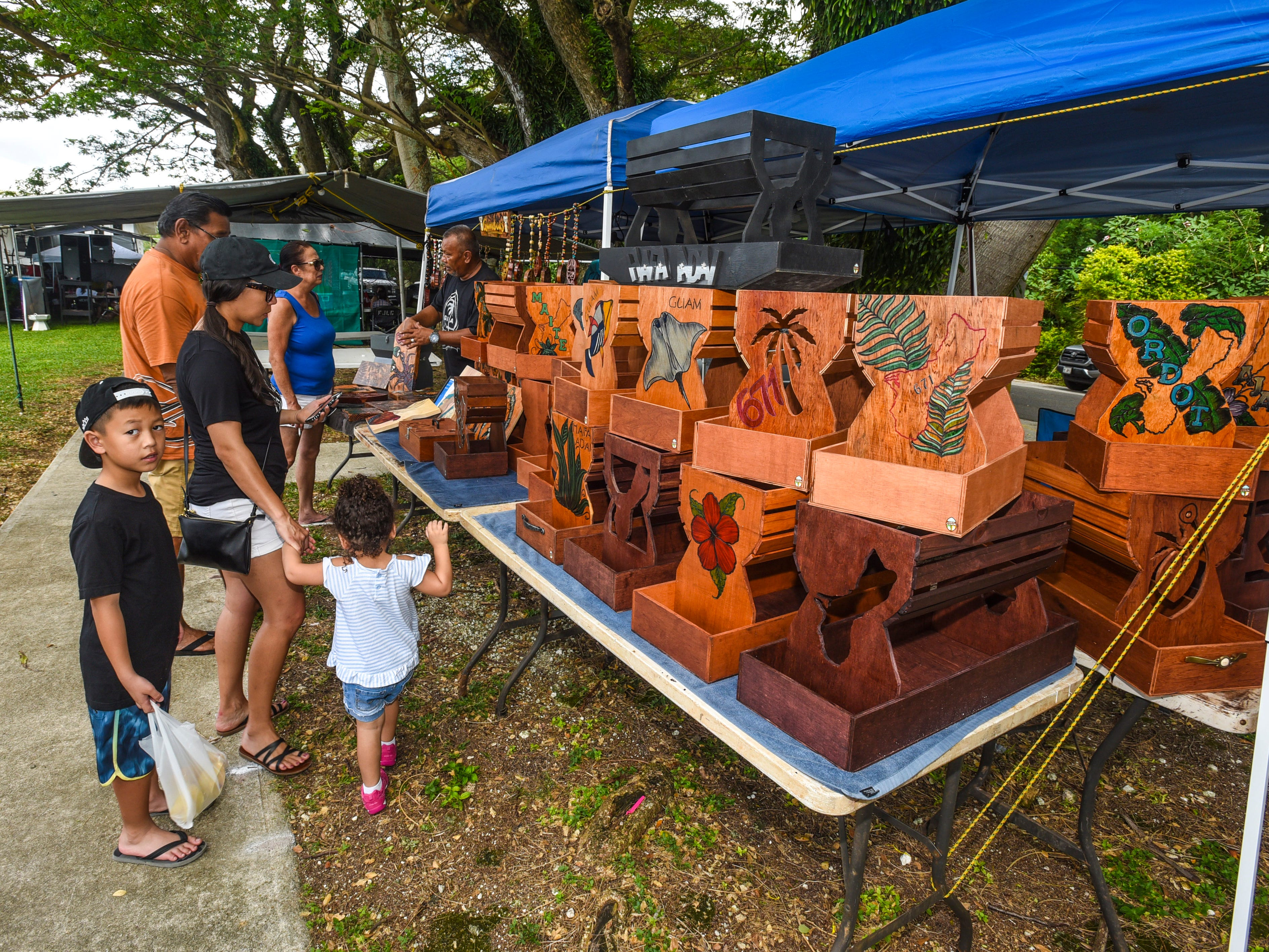 Festival-goers look over paper plate caddies and other wooden products displayed at the Gamboa's Latte Stone Wood Products vendor stand at the annual Malesso Fiestan Tasi on Saturday, Dec. 1, 2018 at the Malesso Veteran Sons & Daughters Pier Park. The village festival is slated to continue on Sunday, Dec. 2, with plans of a spearfishing competition, personal watercraft racing, live entertainment and an evening fireworks show being held.