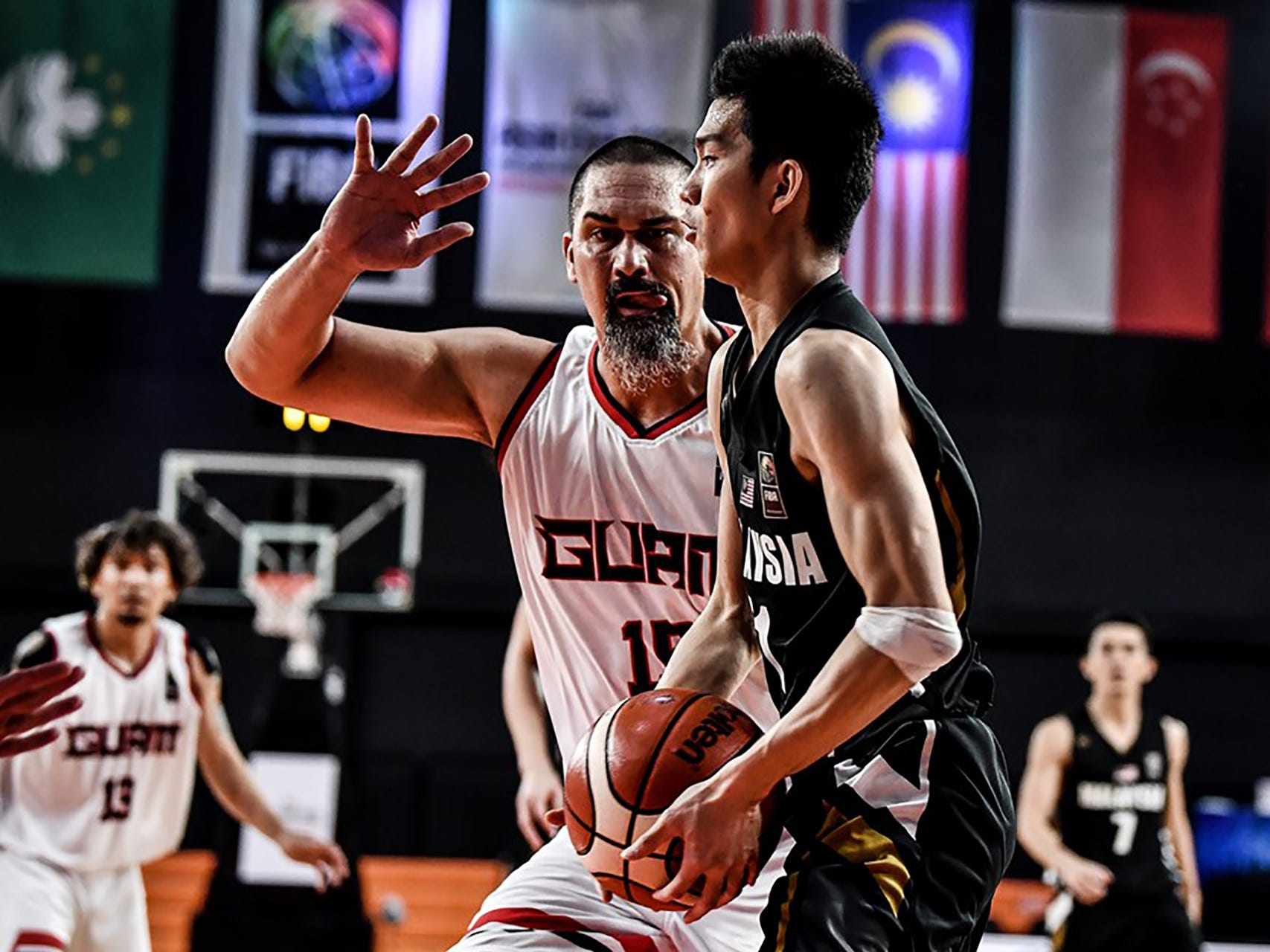 Team Guam big man Mekeli Wesley dwarfs Malaysia's Yi Hoiu Wong during Guam's final game against Malaysia. Guam won 101-78 to complete a 6-0 sweep of all teams in  Asia's Eastern Division and move on to the qualifier round of the FIBA Asia Cup 2021.