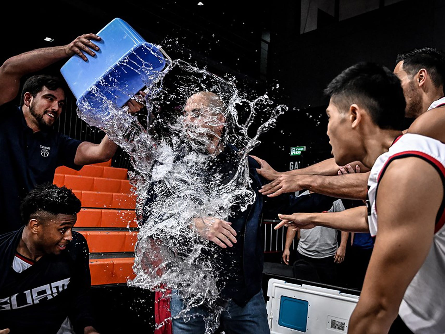 Team Guam manager Seve Susuico douses head coach EJ Calvo with a bucket of water as Earnest Ross, below, moves out of the way.