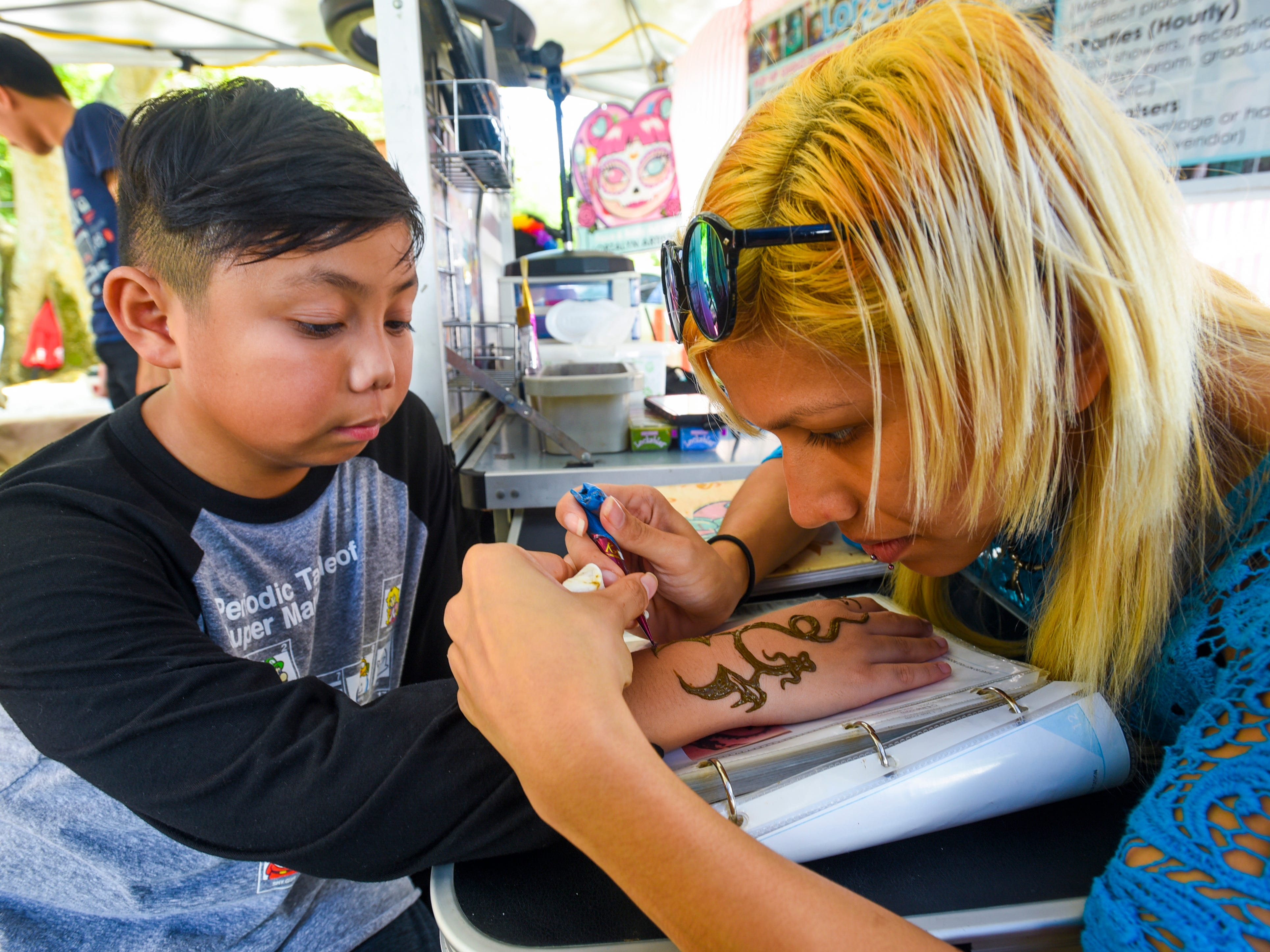Caelan Borja, 10, gets a detailed henna tattoo of a dragon, by artisan Alexis Cruz, during the annual Malesso Fiestan Tasi on Saturday, Dec. 1, 2018 at the Malesso Veteran Sons & Daughters Pier Park. The village festival is slated to continue on Sunday, Dec. 2, with plans of a spearfishing competition, personal watercraft racing, live entertainment and an evening fireworks show being held.
