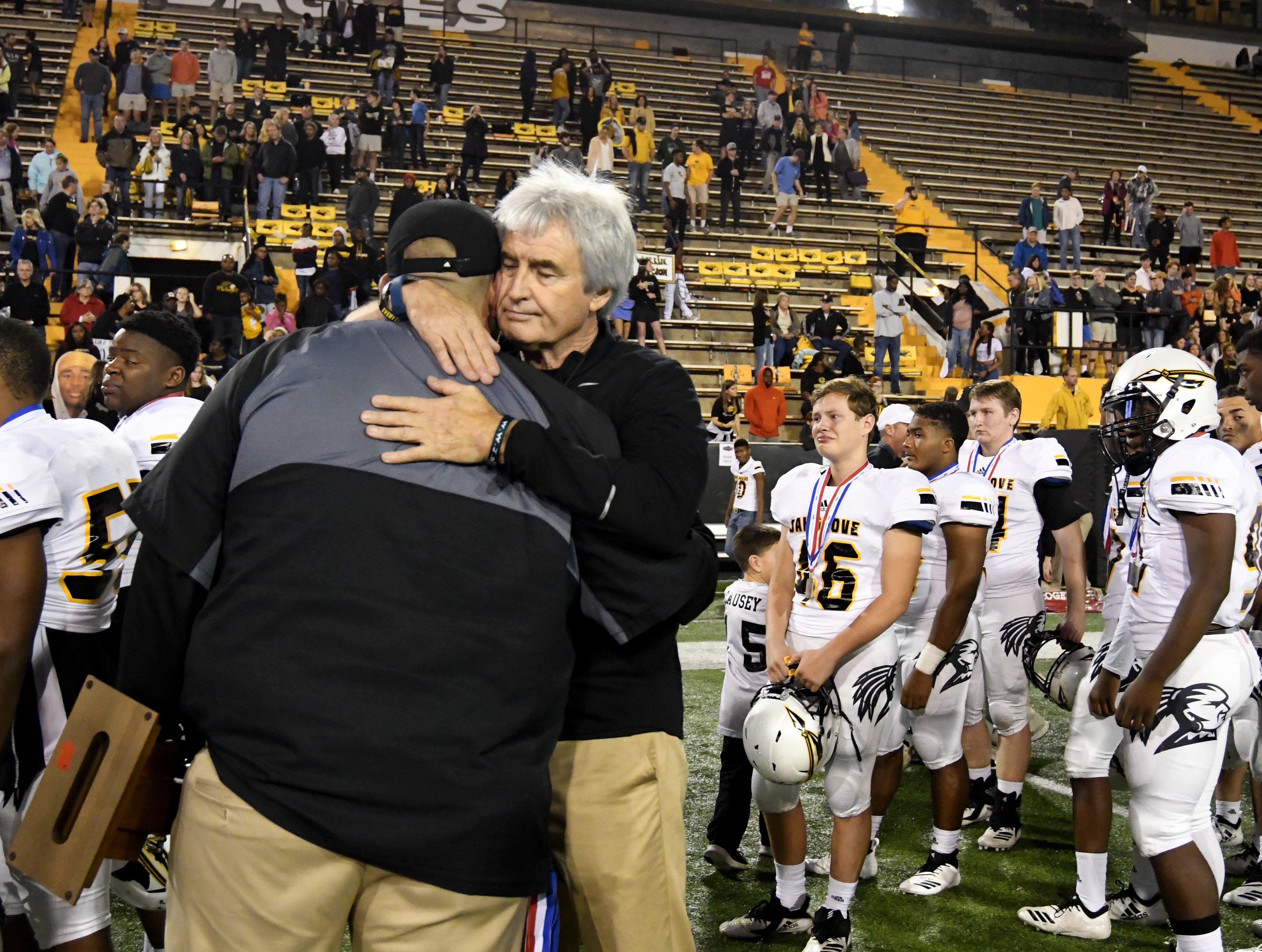 Retired Oak Grove coach Nevil Barr comforts current head coach Drew Casey after losing to Horn Lake  in the 6A state championship game at M.M. Roberts Stadium in Hattiesburg on Friday, November 30, 2018.