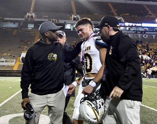 Oak Grove quarterback John Rhys Plumlee is comforted by staff members after losing to Horn Lake in the 6A state championship game at M.M. Roberts Stadium in Hattiesburg on Friday, November 30, 2018.