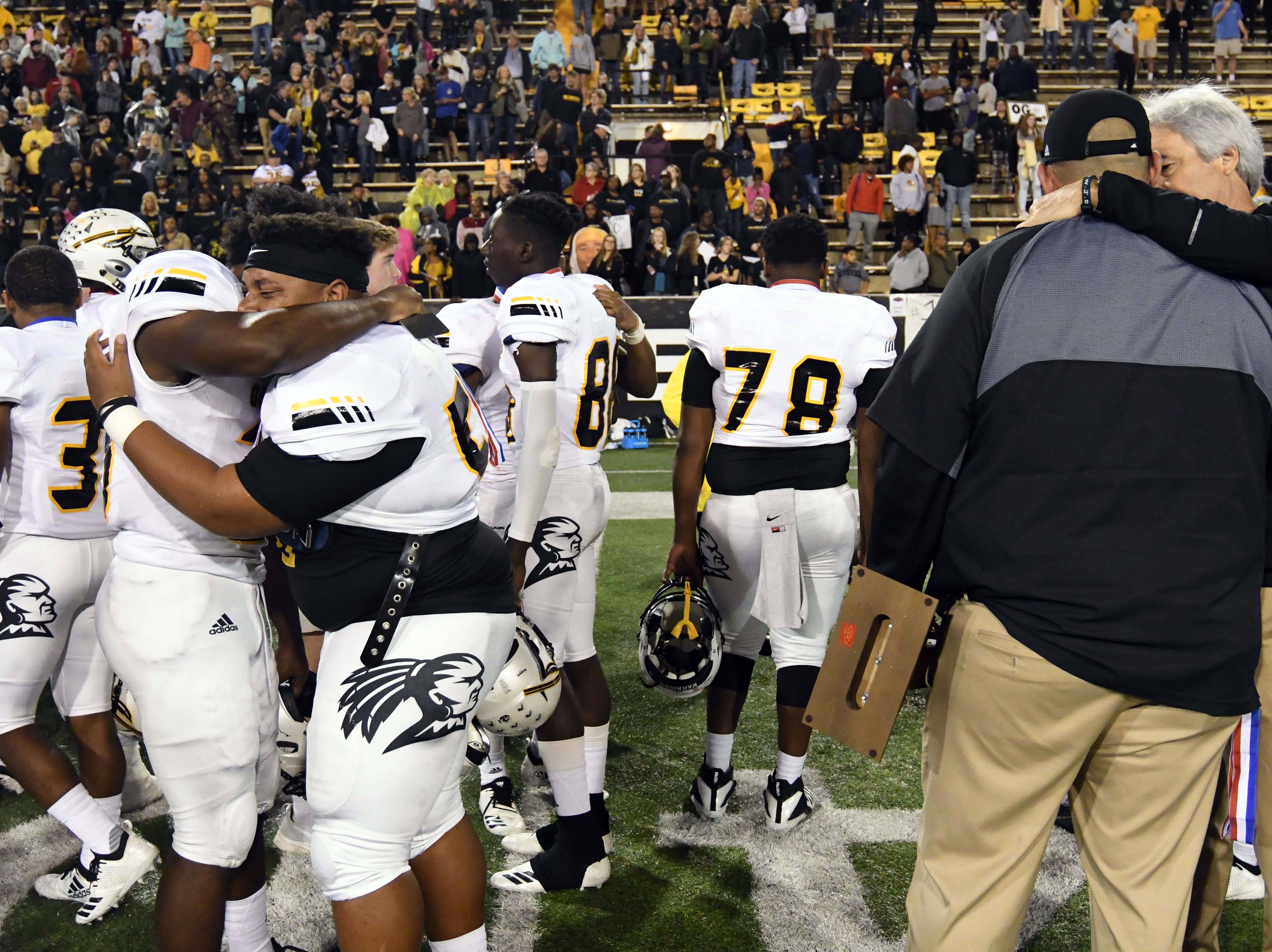 Oak Grove players and coaches comfort each other after losing to Horn Lake  in the 6A state championship game at M.M. Roberts Stadium in Hattiesburg on Friday, November 30, 2018.