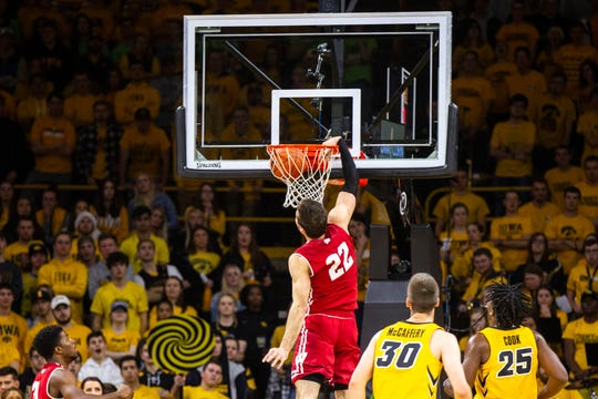 Wisconsin's Ethan Happ (22) dunks past Iowa guard Connor McCaffery (30) and Iowa forward Tyler Cook (25) during a NCAA Big Ten Conference men's basketball game on Friday, Nov. 30, 2018, at Carver-Hawkeye Arena in Iowa City.
