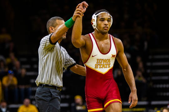 Iowa State's Marcus Coleman has his arm raised after Iowa has an injury default at 174 during a NCAA Cy-Hawk series wrestling dual on Saturday, Dec. 1, 2018, at Carver-Hawkeye Arena in Iowa City.