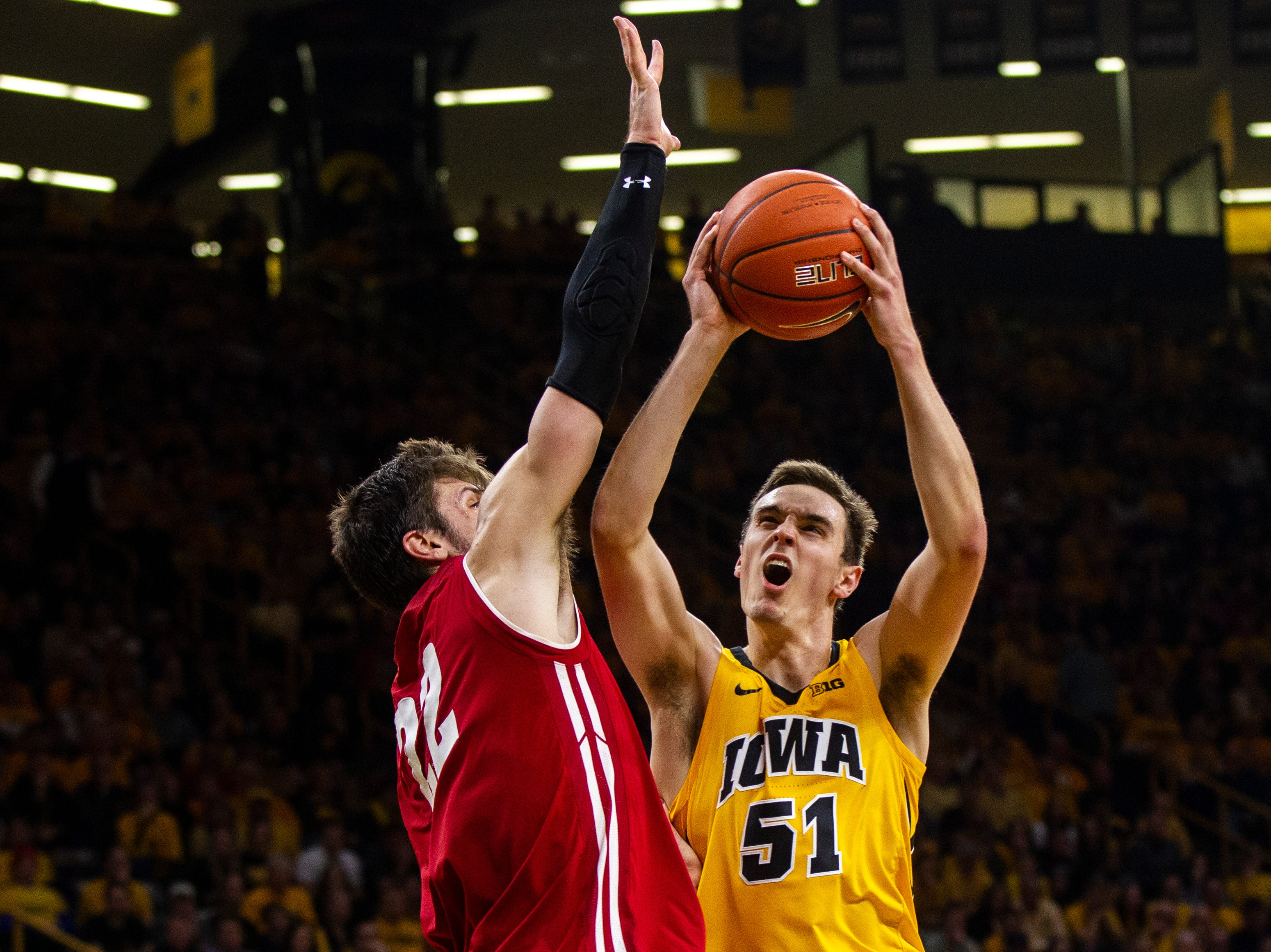 Iowa forward Nicholas Baer (51) drives to the hoop past Wisconsin's Ethan Happ (22) during a NCAA Big Ten Conference men's basketball game on Friday, Nov. 30, 2018, at Carver-Hawkeye Arena in Iowa City.