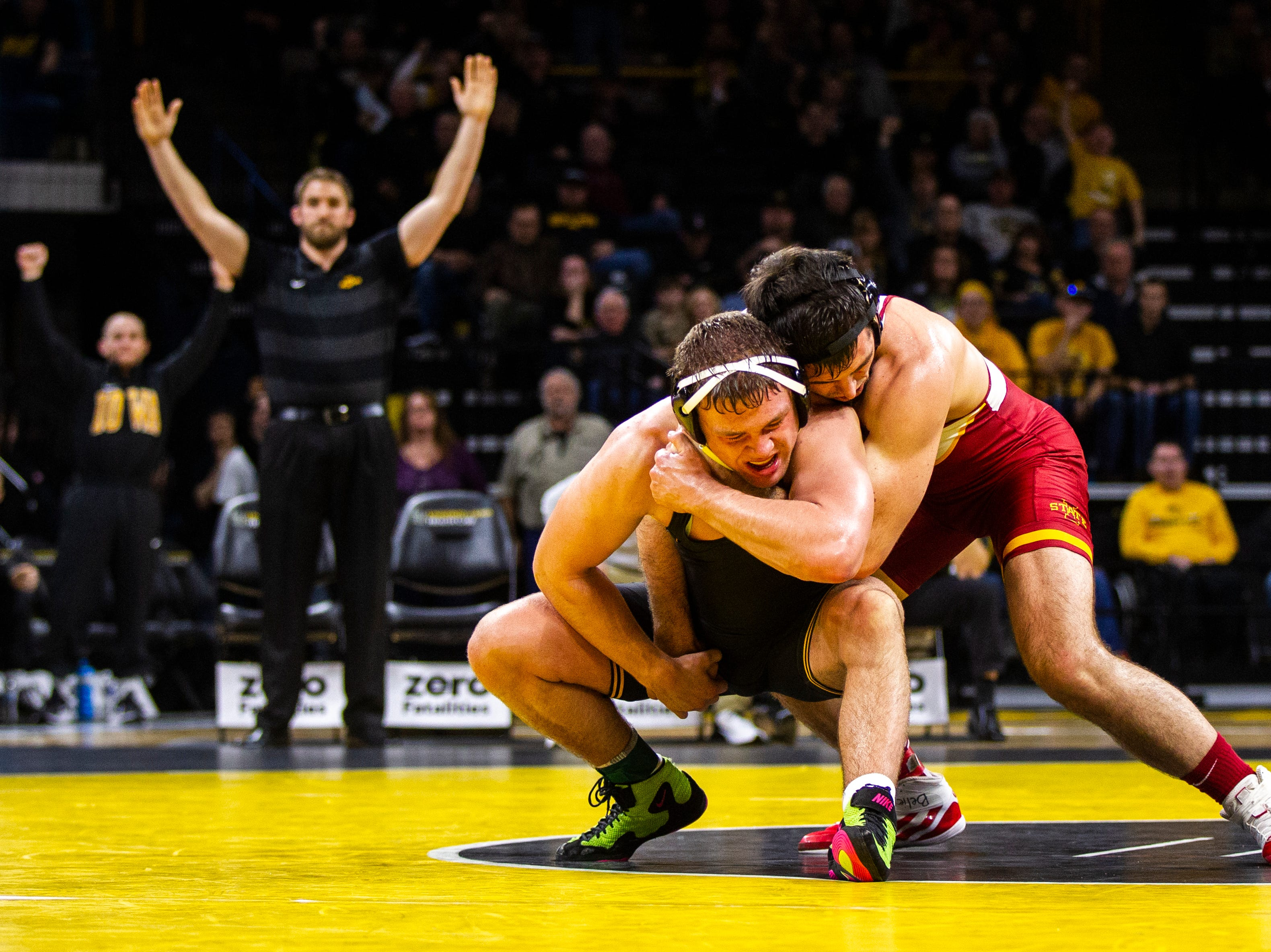 Iowa's Jacob Warner, left, wrestles Iowa State's Willie Miklus at 197 while Iowa volunteer assistant coach Bobby Telford gestures in the background during a NCAA Cy-Hawk series wrestling dual on Saturday, Dec. 1, 2018, at Carver-Hawkeye Arena in Iowa City.