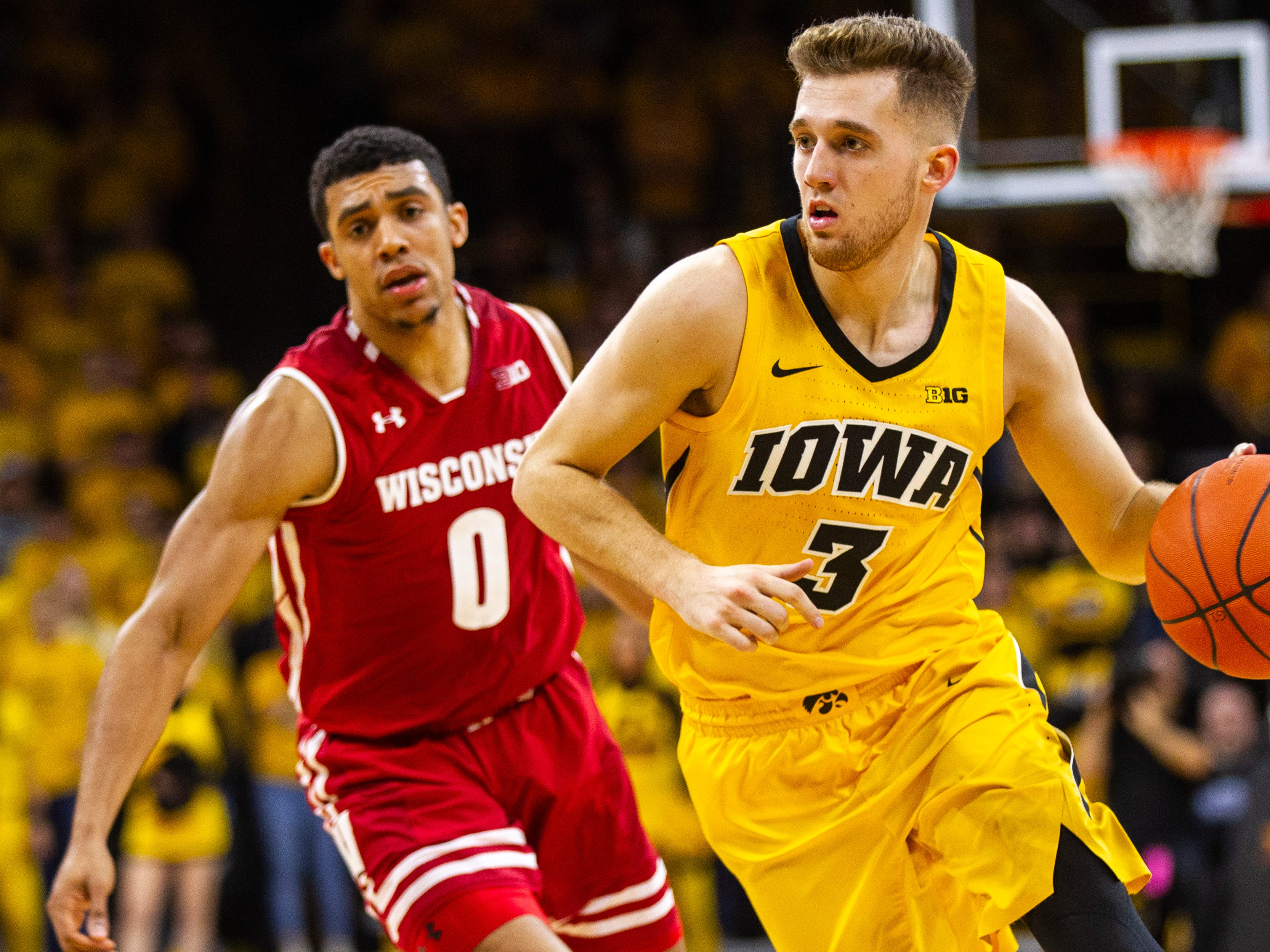 Iowa guard Jordan Bohannon (3) drives to the hoop past Wisconsin's D'Mitrik Trice (0) during a NCAA Big Ten Conference men's basketball game on Friday, Nov. 30, 2018, at Carver-Hawkeye Arena in Iowa City.