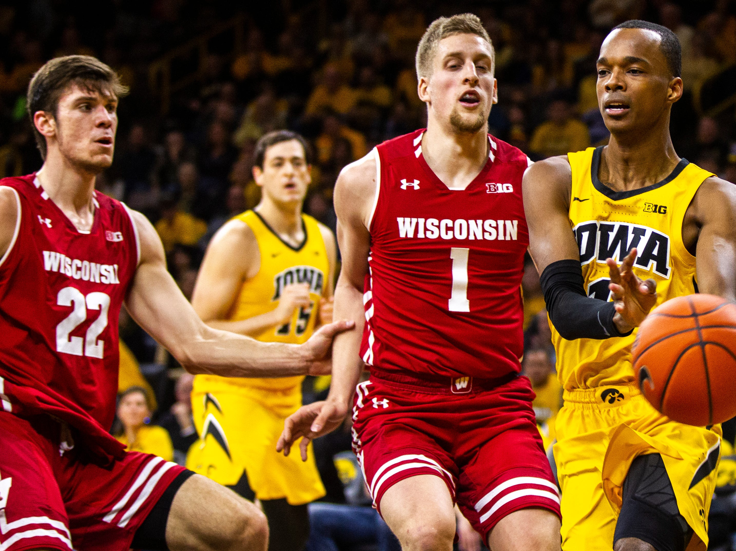Iowa guard Maishe Dailey (1) passes while being defended by Wisconsin's Brevin Pritzl (1) during a NCAA Big Ten Conference men's basketball game on Friday, Nov. 30, 2018, at Carver-Hawkeye Arena in Iowa City.