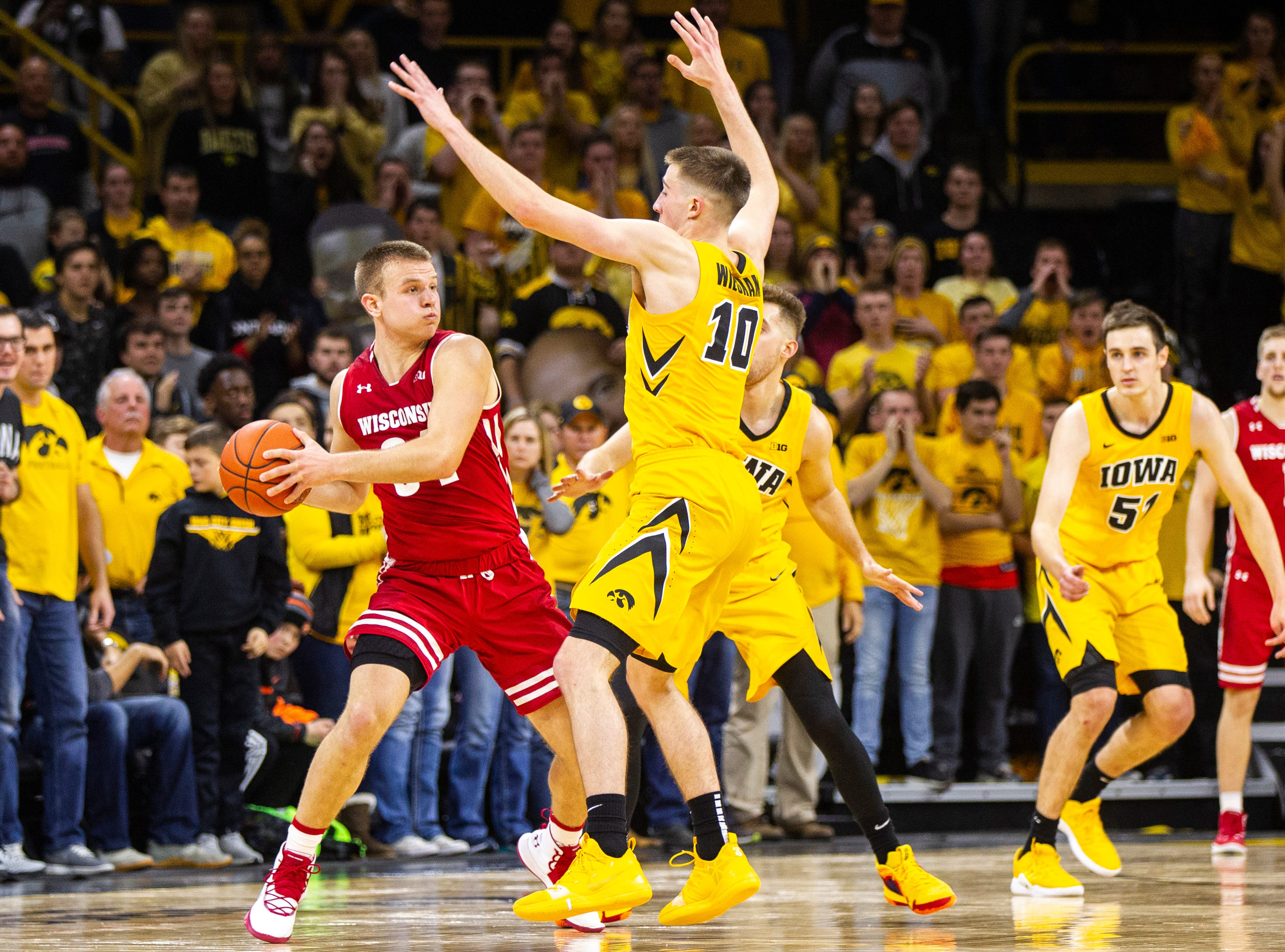 Wisconsin's Brad Davidson (34) looks to pass while being defended by Iowa guard Joe Wieskamp (10) and Iowa guard Jordan Bohannon (3) during a NCAA Big Ten Conference men's basketball game on Friday, Nov. 30, 2018, at Carver-Hawkeye Arena in Iowa City.
