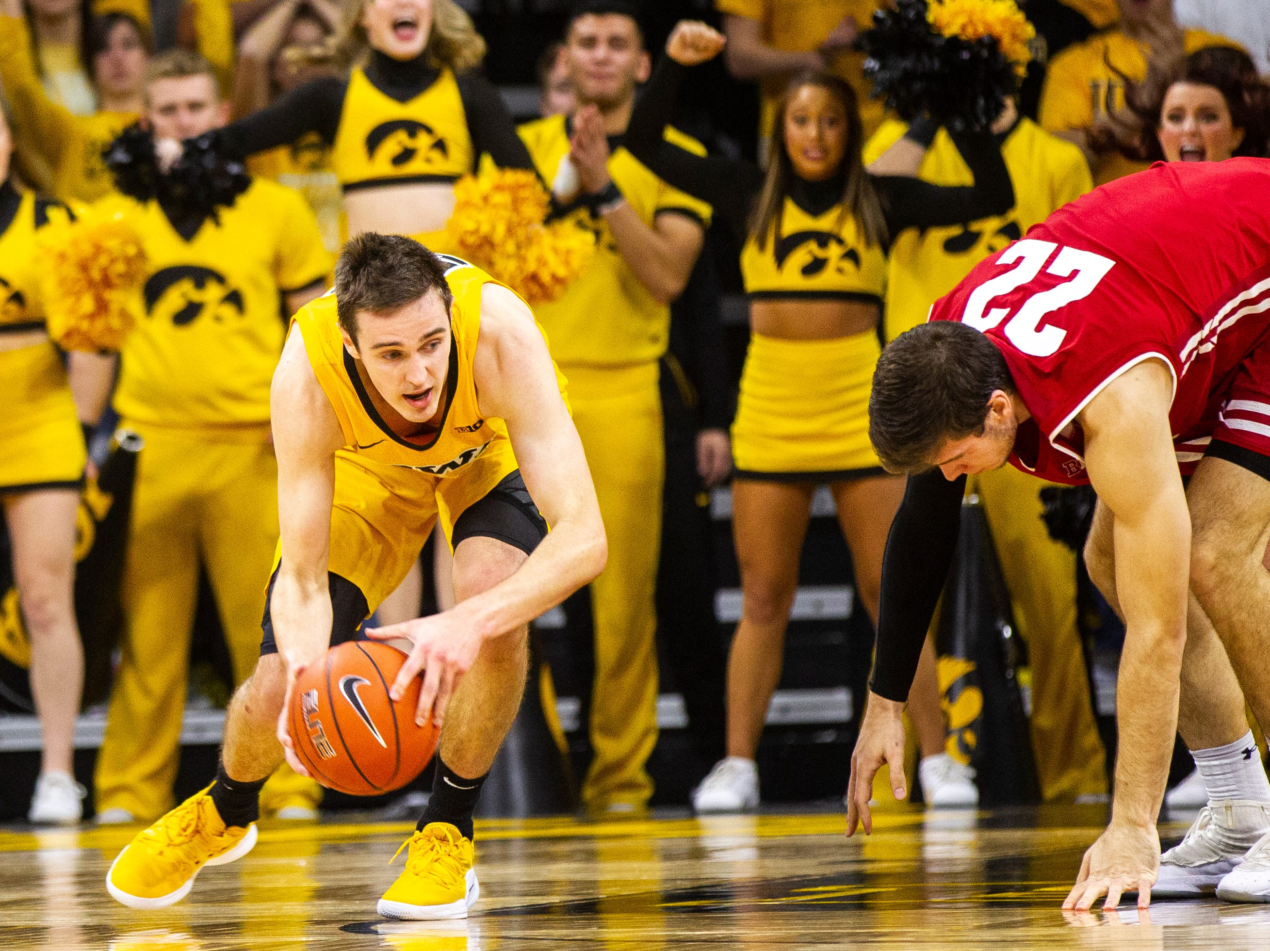Iowa forward Nicholas Baer (51) gets a steal from Wisconsin's Ethan Happ (22) during a NCAA Big Ten Conference men's basketball game on Friday, Nov. 30, 2018, at Carver-Hawkeye Arena in Iowa City.