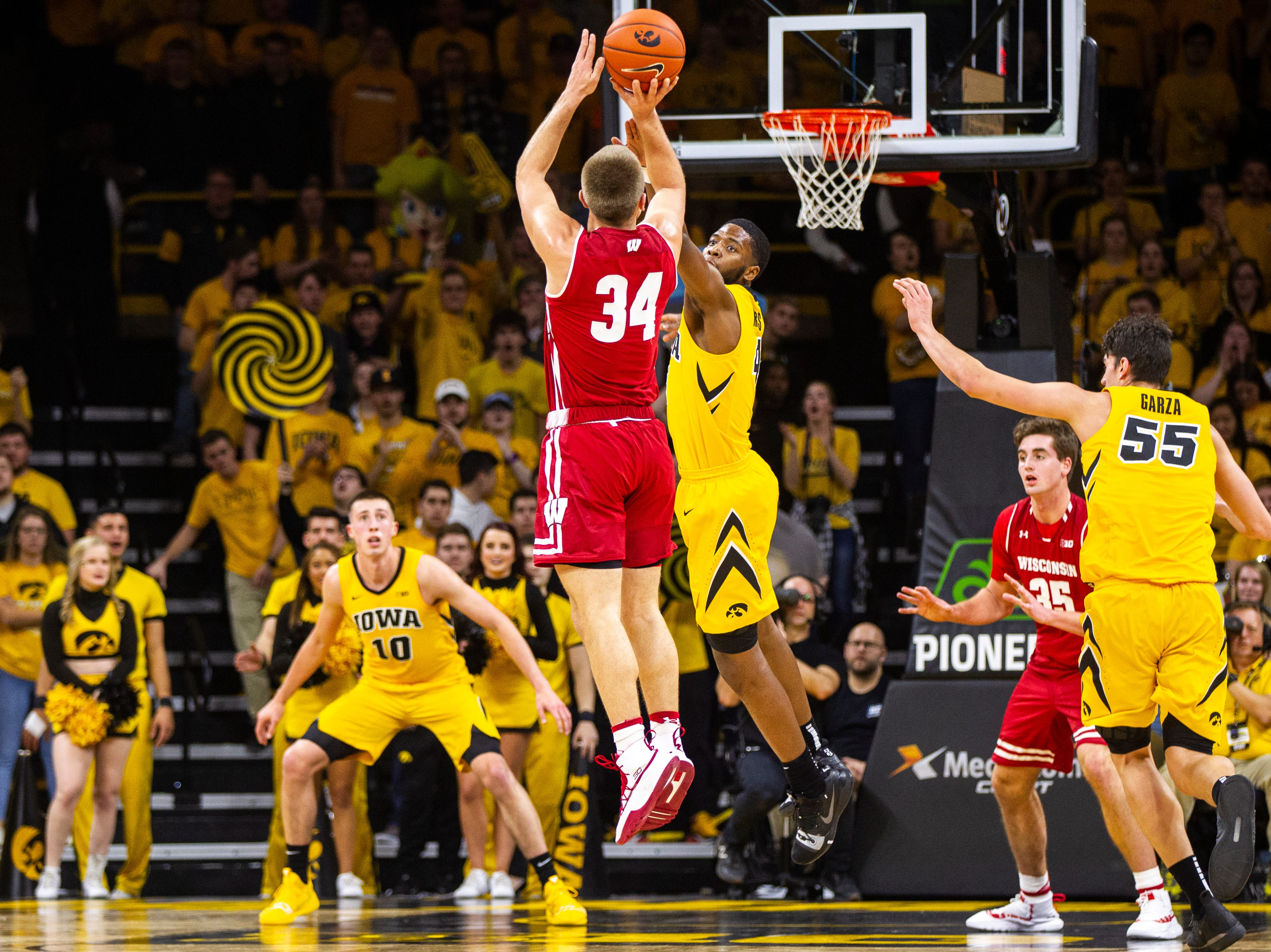 Wisconsin's Brad Davidson (34) attempts a 3-point basket over Iowa guard Isaiah Moss (4) during a NCAA Big Ten Conference men's basketball game on Friday, Nov. 30, 2018, at Carver-Hawkeye Arena in Iowa City.