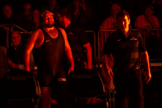 Iowa's Sam Stoll, left, is introduced as Iowa head coach Tom Brands walks out ahead of him during a NCAA Cy-Hawk series wrestling dual on Saturday, Dec. 1, 2018, at Carver-Hawkeye Arena in Iowa City.