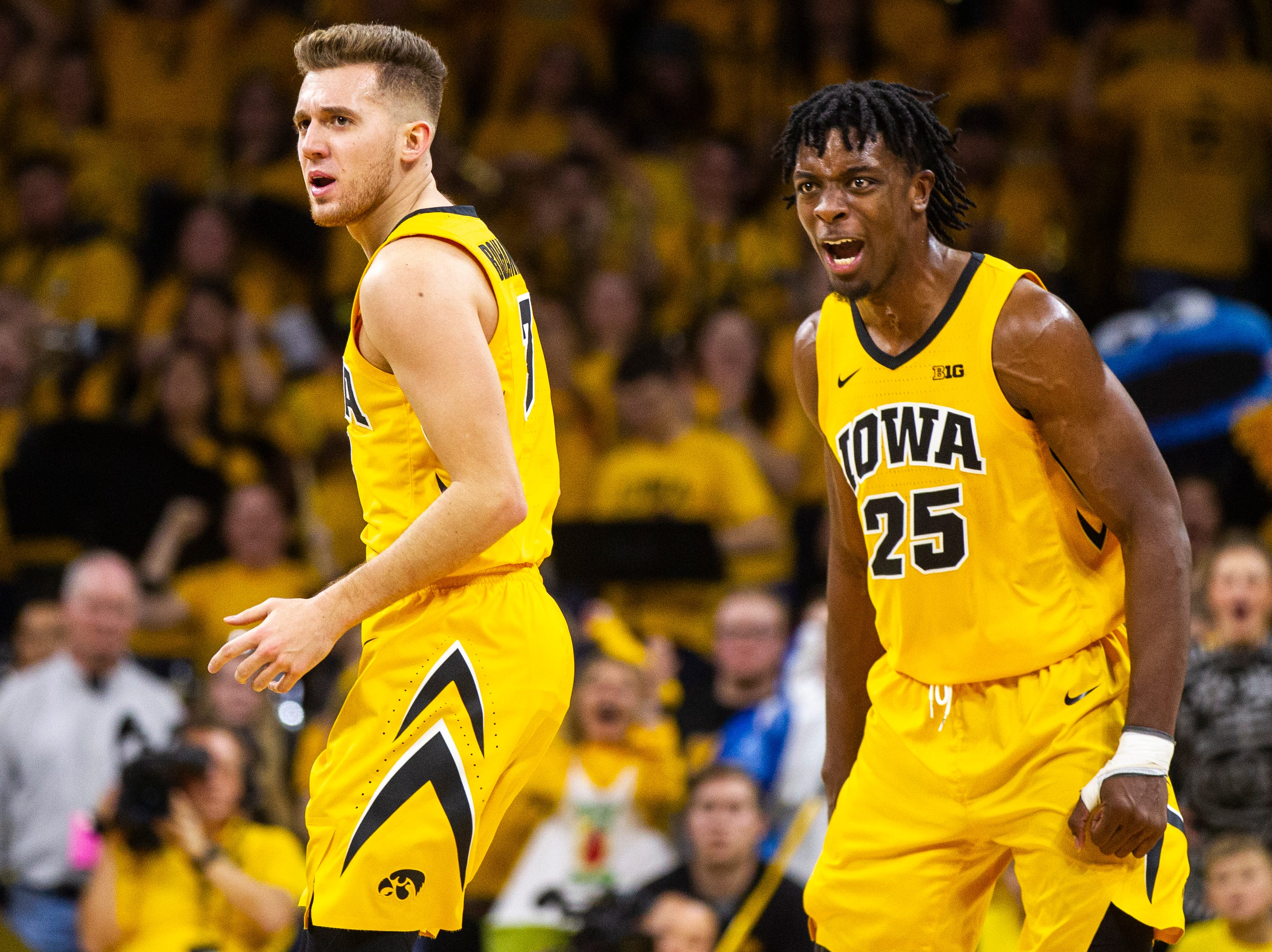 Iowa forward Tyler Cook (25) celebrates with Iowa guard Jordan Bohannon (3) during a NCAA Big Ten Conference men's basketball game on Friday, Nov. 30, 2018, at Carver-Hawkeye Arena in Iowa City.