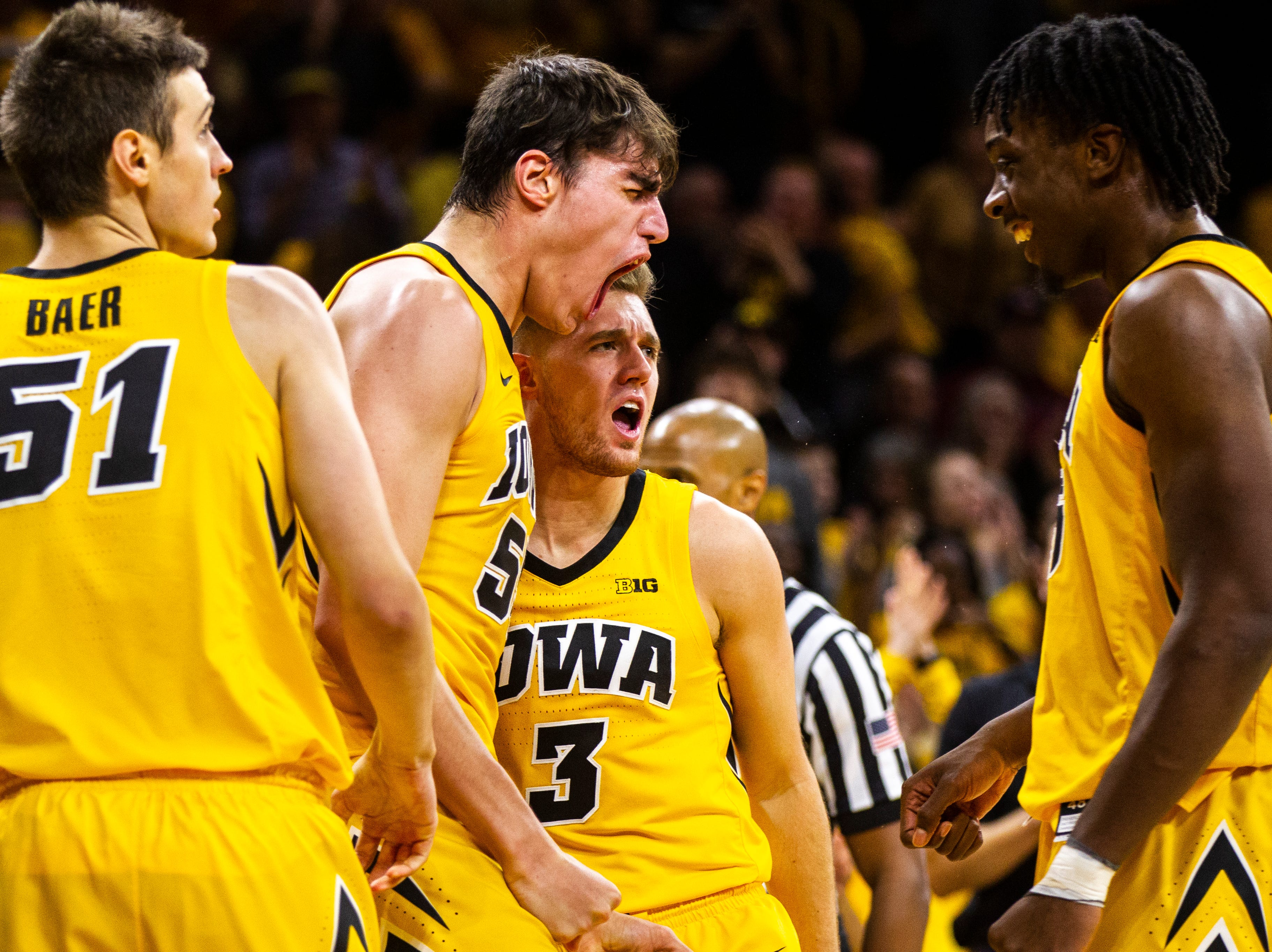 Iowa forward Luka Garza (55) celebrates with Iowa forward Tyler Cook (25) and Iowa guard Jordan Bohannon (3) after drawing a foul during a NCAA Big Ten Conference men's basketball game on Friday, Nov. 30, 2018, at Carver-Hawkeye Arena in Iowa City.
