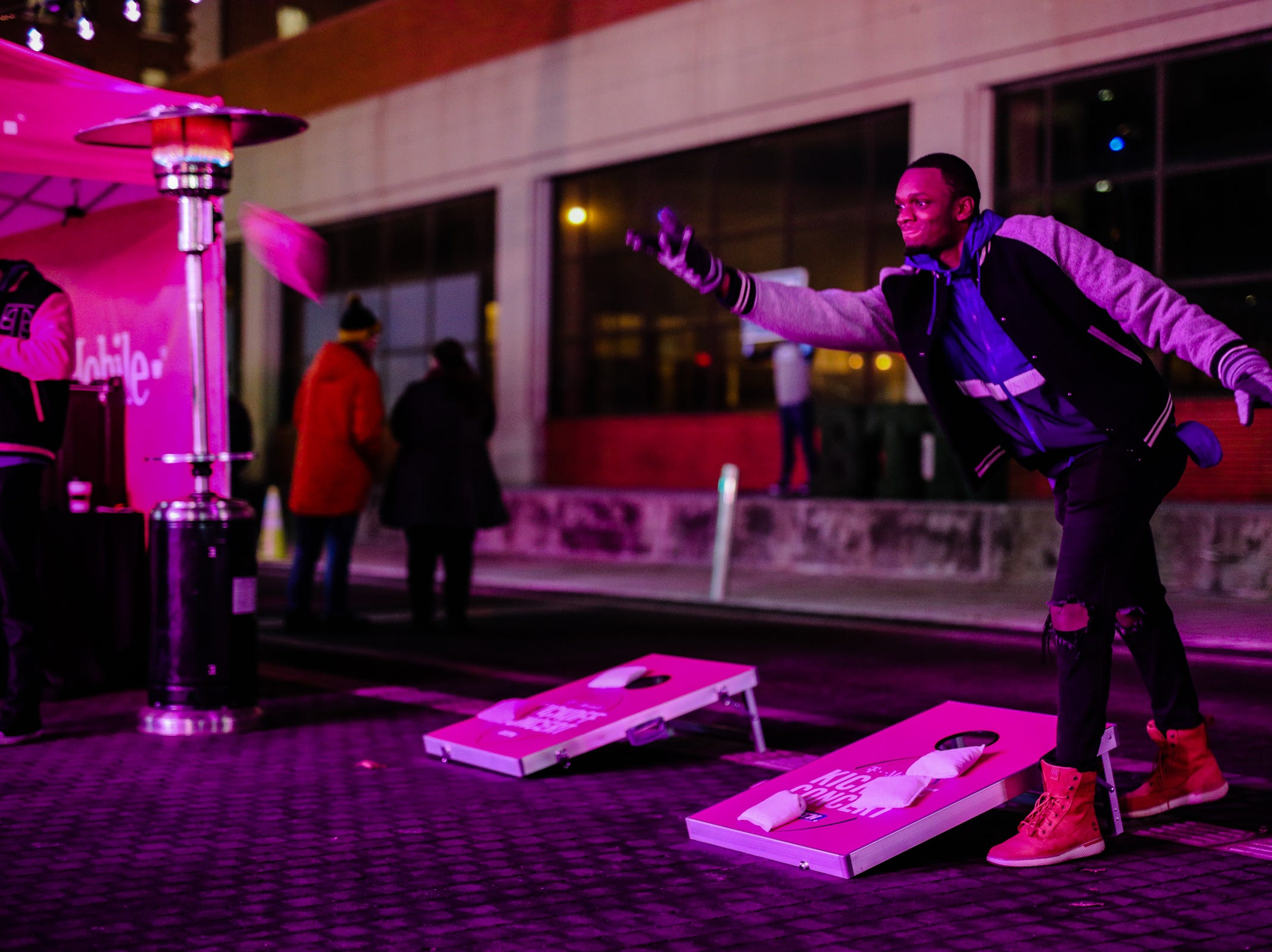 Cornhole is played under a pink glow during the Georgia Street Preshow Tailgate on Friday. Josh Hicks/for Indy Star