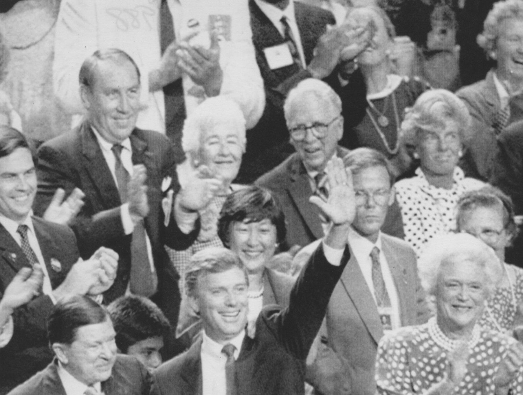Sen. Dan Quayle of Indiana shakes hands with former Sen. John Tower of Texas with one hand and waves to the assembled delegates with the other during the Republican National Convention in New Orleans on Aug. 17, 1988. Quayle, selected by George Bush to be his running mate, sat with Barbara Bush, right, to witness the presidential nomination roll call.