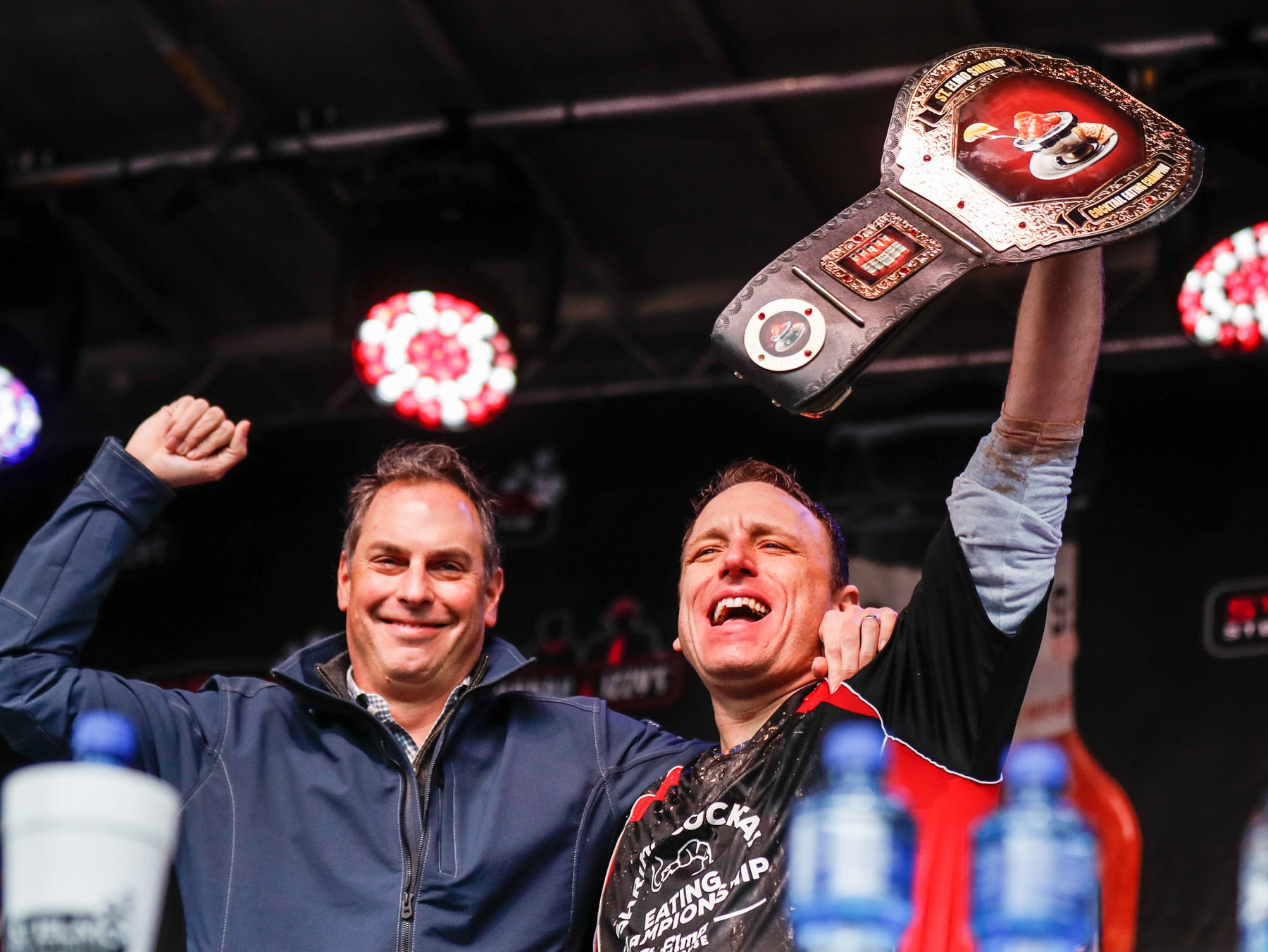 St. Elmo's owner Craig Huse, left, awards Major League Eater, and contest winner Joey Chestnut, right, the championship belt during the sixth annual World Famous St. Elmo Shrimp Cocktail Eating Championship, held during the Meijer Tailgate Party on Georgia St. in Indianapolis on Saturday, Dec. 1, 2018.