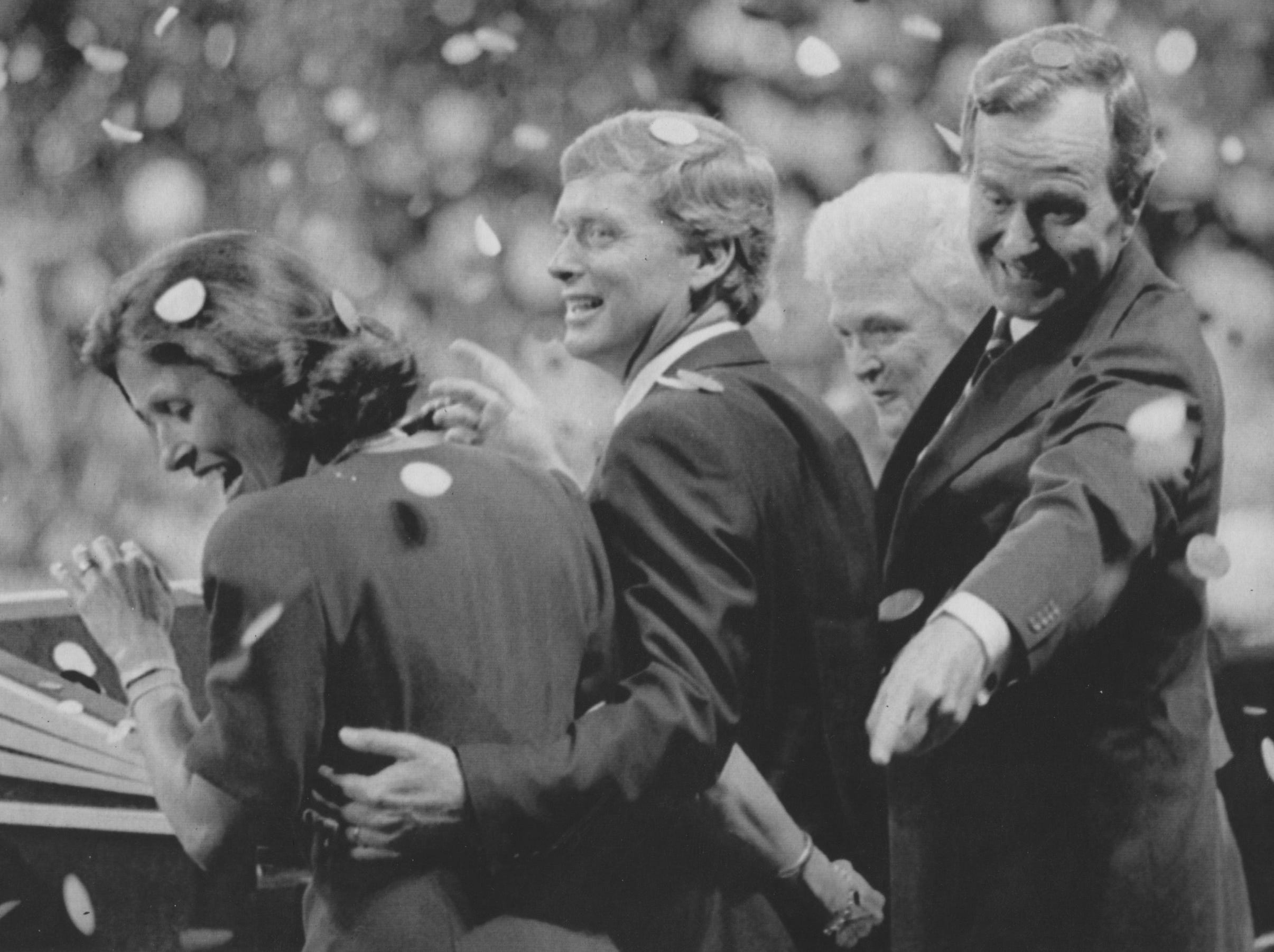 Republican presidential candidate George H. W. Bush points behind the back of his running mate, Sen. Dan Quayle of Indiana, as they and their wives, Marilyn Quayle, left, and Barbara Bush, are showered with confetti at the end of the Republican National Convention on Aug. 18, 1988, in New Orleans.
