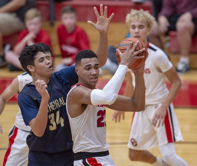 Center Grove High School senior Trayce Jackson-Davis (23) comes down with a rebound as he's defended by Cathedral High School junior Isaac Farah (34) during the second half of action. Center Grove High School hosted Cathedral High School in IHSAA varsity basketball action, Friday, Nov. 30, 2018. Center Grove won 63-60.