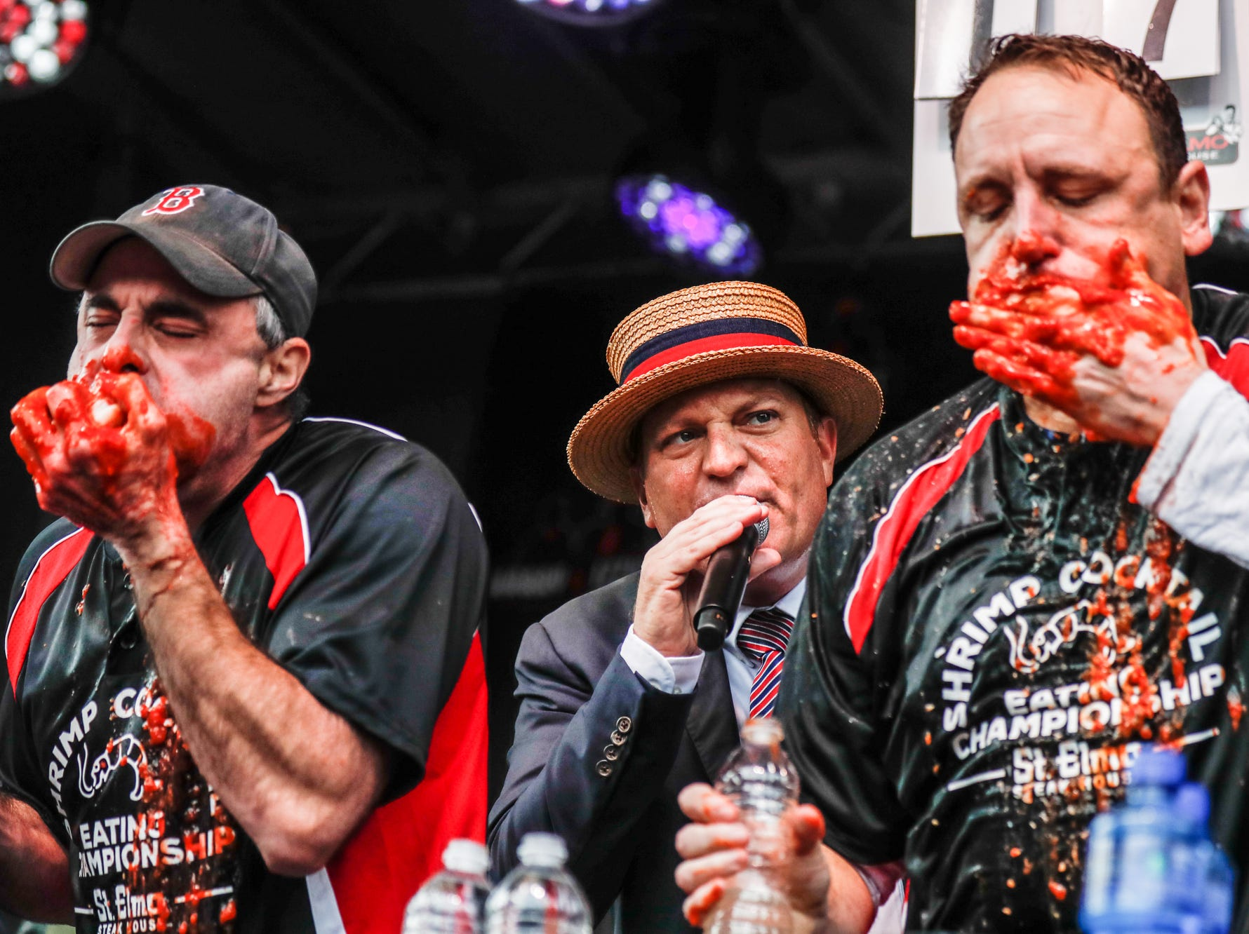 Major League Eaters Geoff Esper (left) and Joey Chestnut are urged on by Major League Eating emcee Sam Barclay during the sixth annual World Famous St. Elmo Shrimp Cocktail Eating Championship, held during the Meijer Tailgate Party on Georgia St. in Indianapolis, on Saturday, Dec. 1, 2018. Chestnut narrowly defeated Esper, setting a new world record, eating 18 pounds and 9.6 ounces of St. Elmo Shrimp Cocktail in 8 minutes.