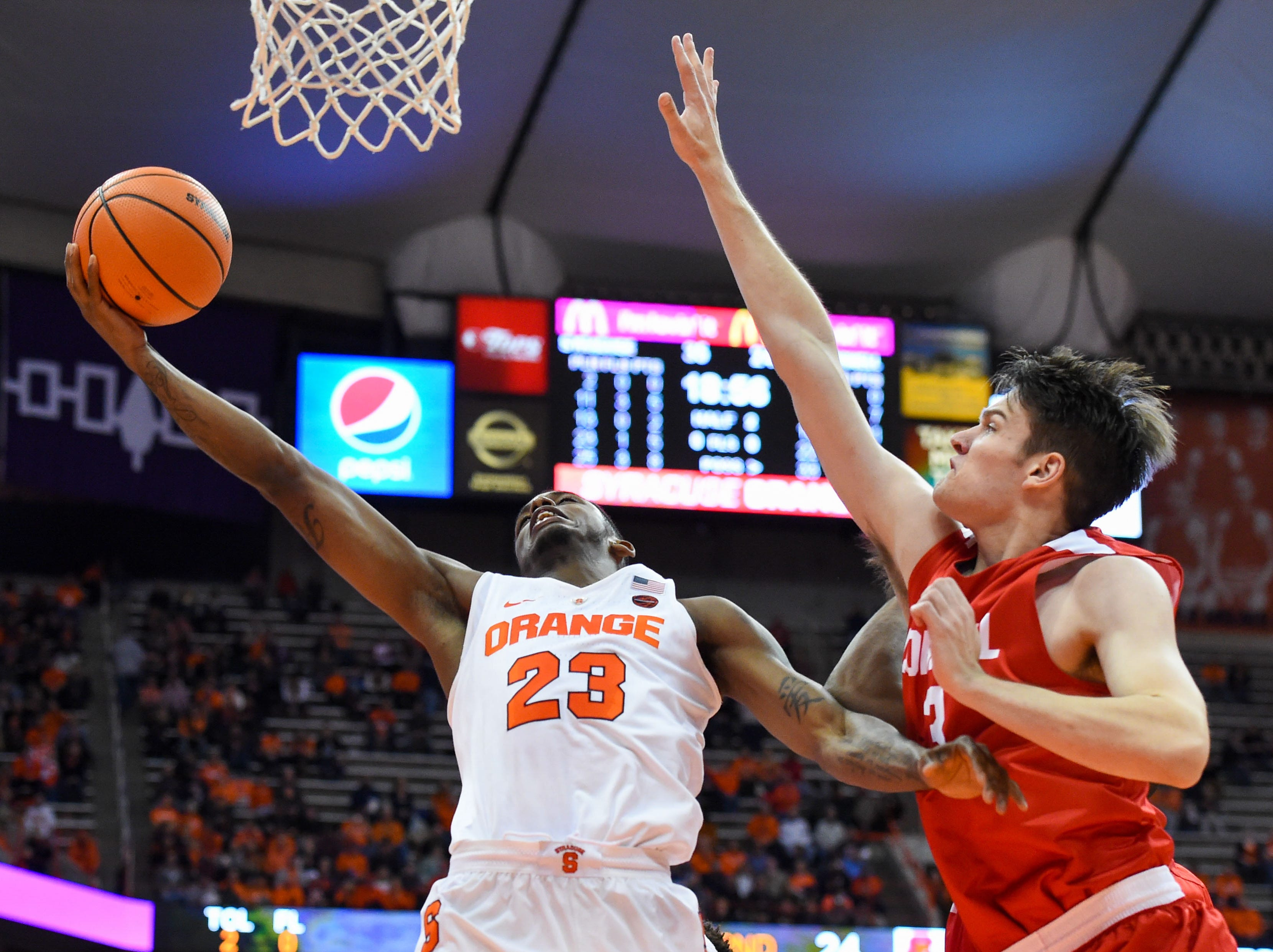 Nov 10, 2017; Syracuse, NY, USA; Syracuse Orange guard Frank Howard (23) shoots the ball around the defense of Cornell Big Red forward Jimmy Boeheim (3) during the second half at the Carrier Dome. Mandatory Credit: Rich Barnes-USA TODAY Sports