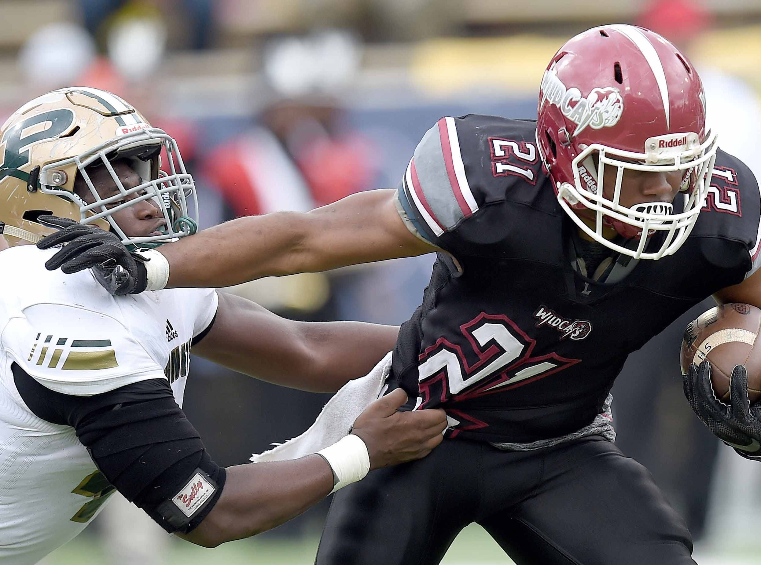 Louisville's Kevon Jackson (21) uses a stiff arm on a Poplarville defender on Saturday, December 1, 2018, in the MHSAA BlueCross BlueShield Gridiron Classic High School Football Championships in M.M. Roberts Stadium on the University of Southern Mississippi campus in Hattiesburg, Miss.