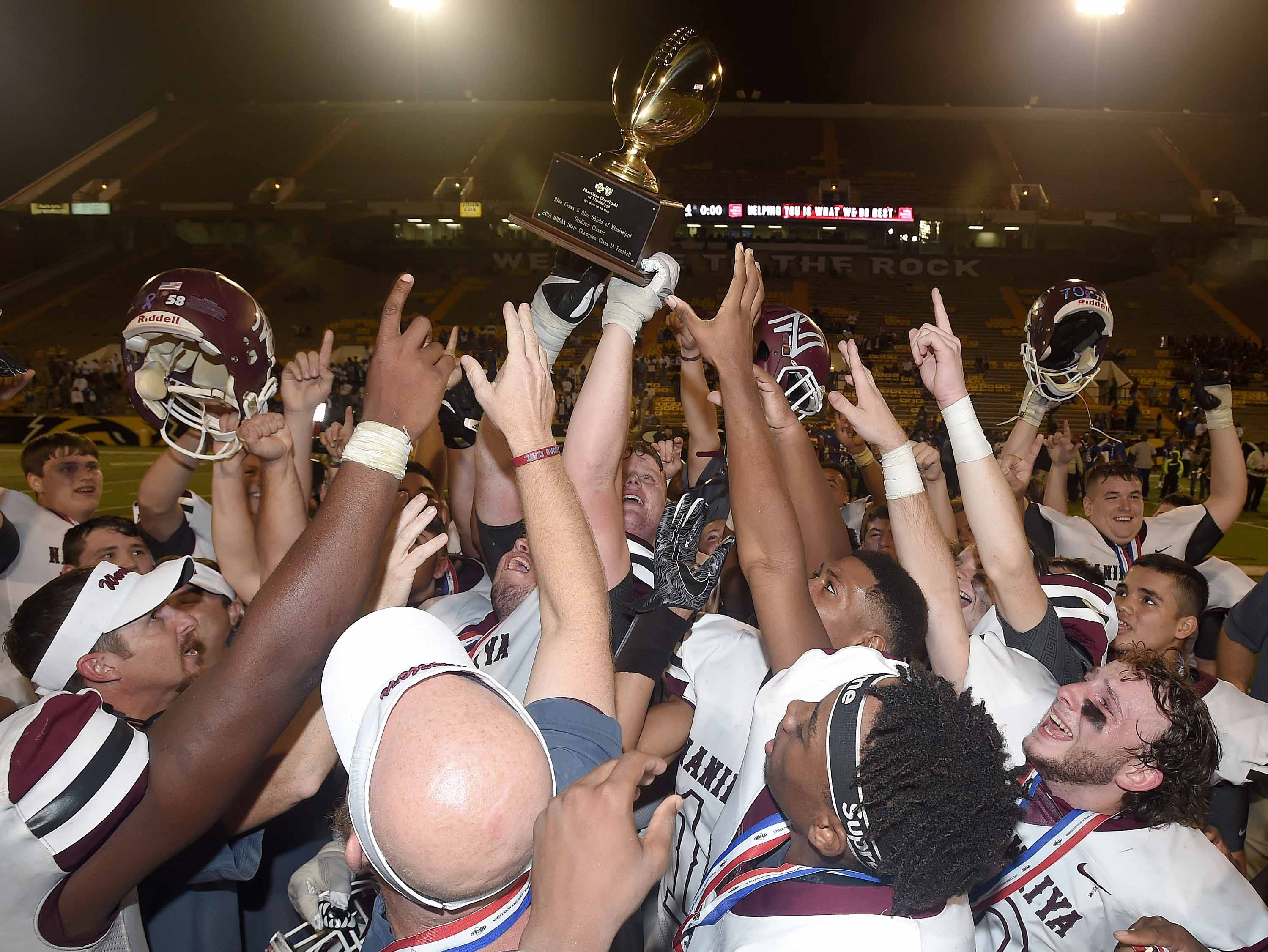 The Nanih Waiya Warriors and head coach James Courtney celebrate with the Class 1A trophy after beating Hollandale Simmons on Friday, November 20, 2018, in the MHSAA BlueCross BlueShield Gridiron Classic High School Football Championships in M.M. Roberts Stadium on the University of Southern Mississippi campus in Hattiesburg, Miss.