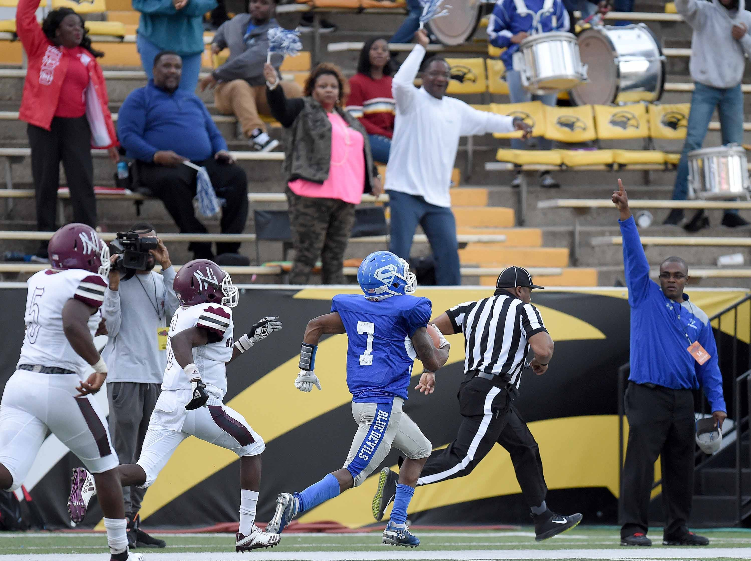 Fans celebrate in the background as Hollandale Simmons' Antavius Rounds (7) runs for a touchdown against Nanih Waiya on Friday, November 20, 2018, in the MHSAA BlueCross BlueShield Gridiron Classic High School Football Championships in M.M. Roberts Stadium on the University of Southern Mississippi campus in Hattiesburg, Miss.