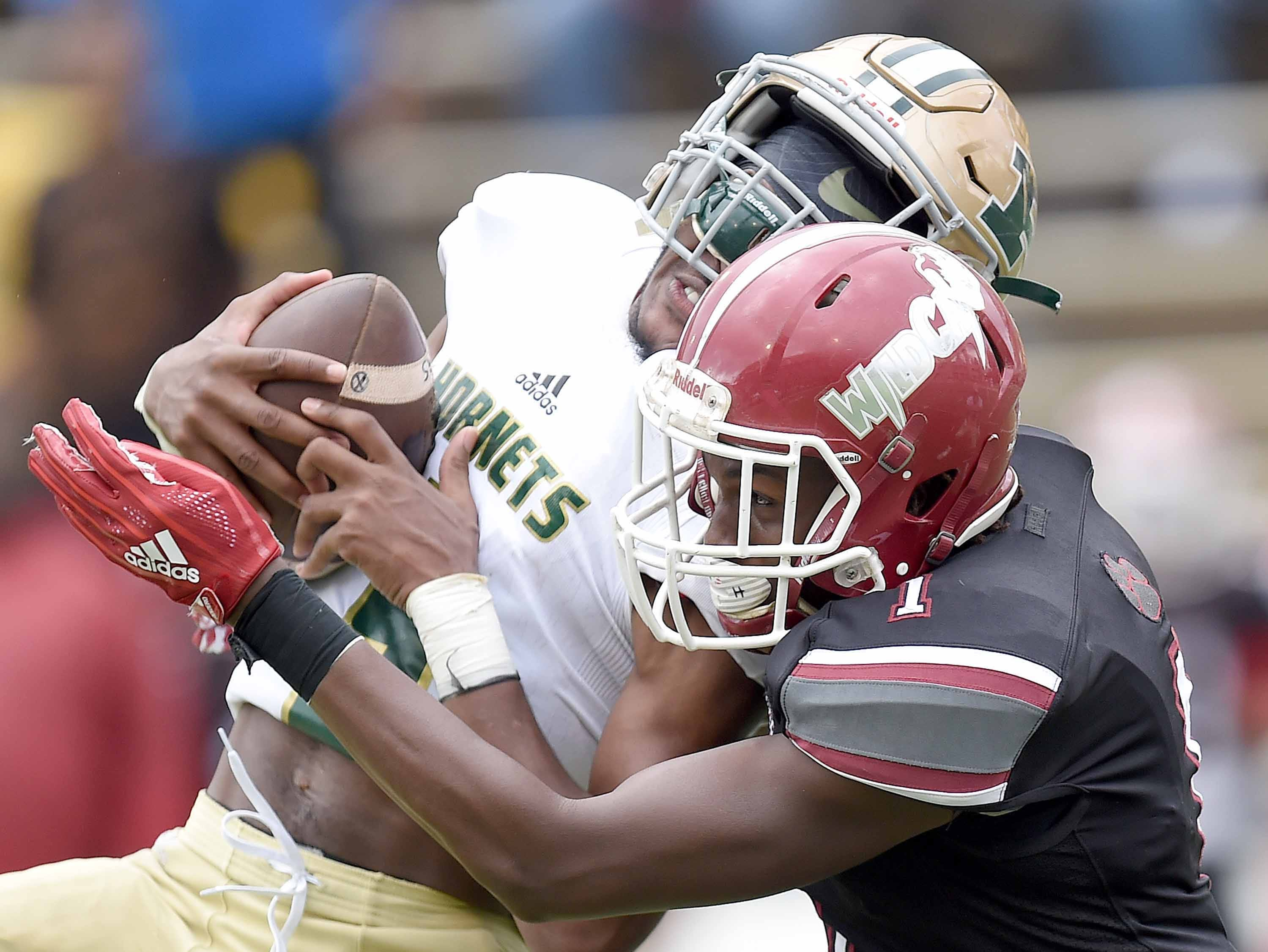Poplarville's Antonio Barnes (left) begins to lose his helmet after intercepting a pass against Louisville on Saturday, December 1, 2018, in the MHSAA BlueCross BlueShield Gridiron Classic High School Football Championships in M.M. Roberts Stadium on the University of Southern Mississippi campus in Hattiesburg, Miss.
