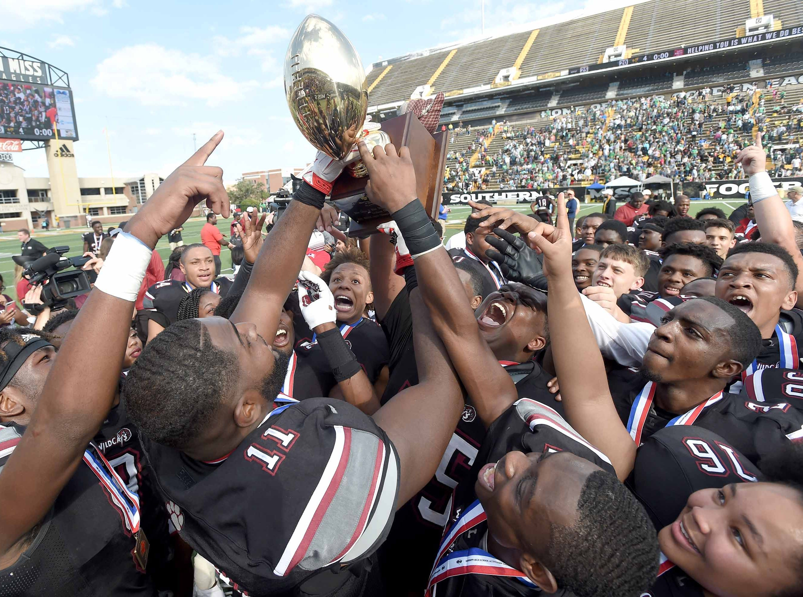 The Louisville Wildcats celebrate with the Class 4A trophy after beating Poplarville on Saturday, December 1, 2018, in the MHSAA BlueCross BlueShield Gridiron Classic High School Football Championships in M.M. Roberts Stadium on the University of Southern Mississippi campus in Hattiesburg, Miss.