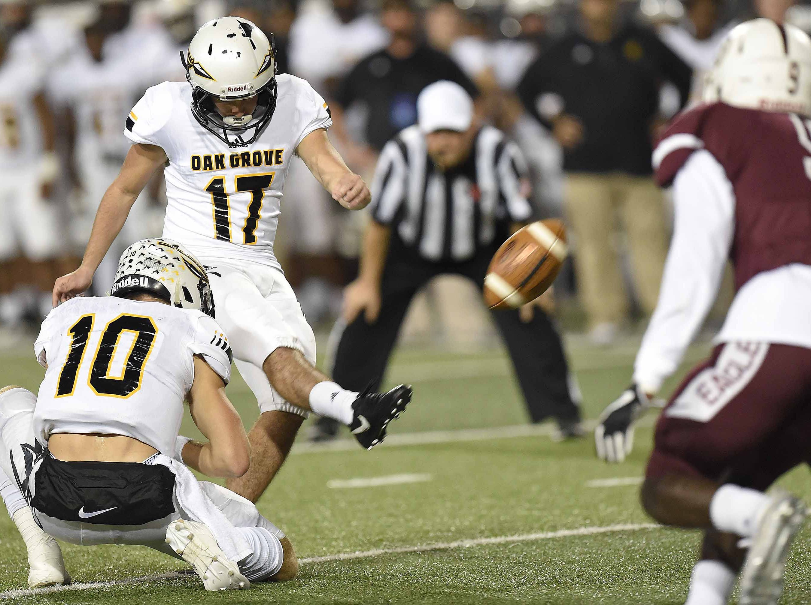 Oak Grove's Blake Ortego (17) kicks an extra point out of the hold by John Rhys Plumlee (10) on Friday, November 20, 2018, in the MHSAA BlueCross BlueShield Gridiron Classic High School Football Championships in M.M. Roberts Stadium on the University of Southern Mississippi campus in Hattiesburg, Miss.