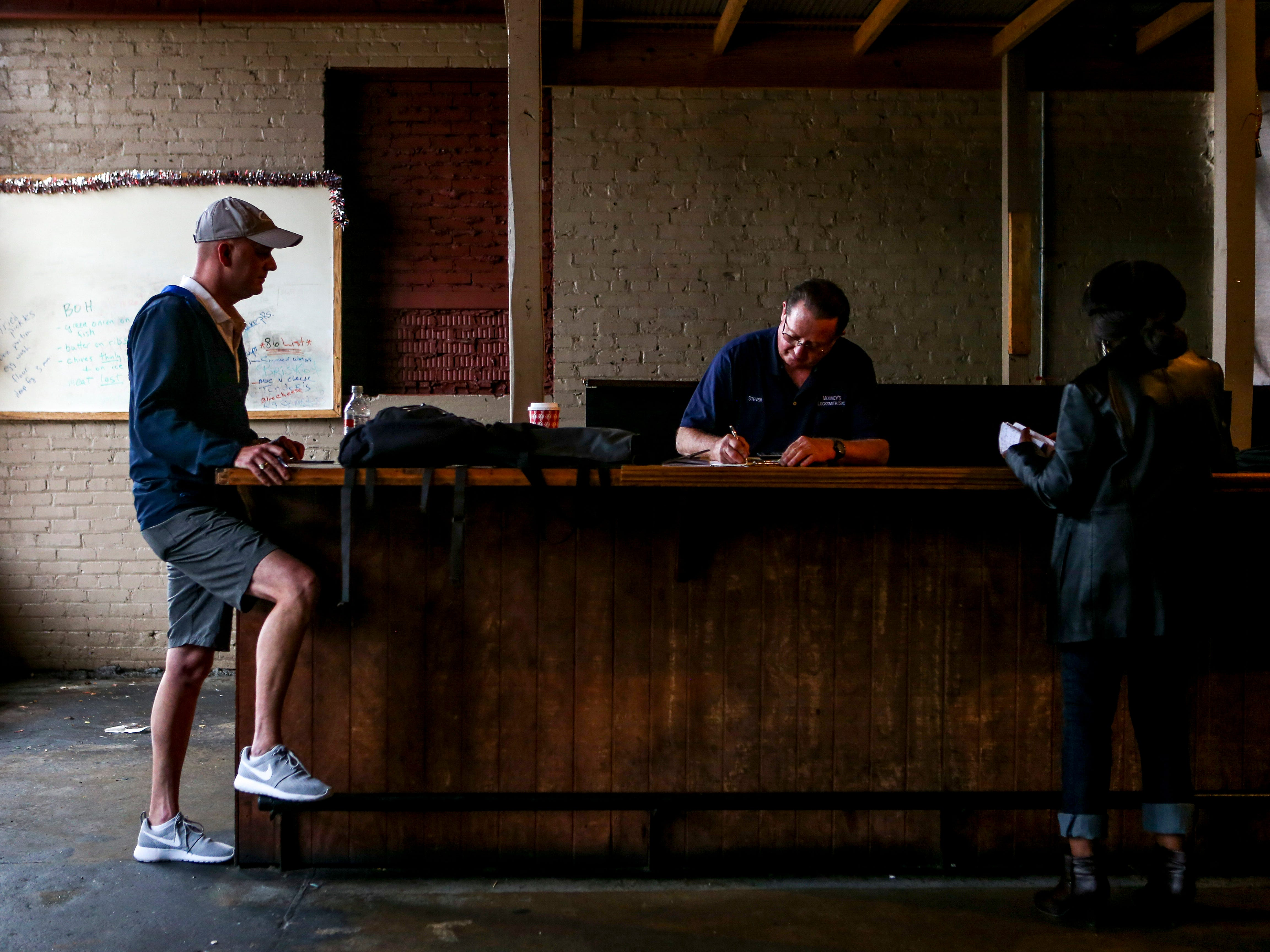 Drew Baker, the new owner of the building downtown, Steve Mooney, center, a locksmith that built the news keys for the location, and Katie Brantley, right, hang out during the finalizing of creating new keys at West Alley BBQ in Jackson, Tenn., on Friday, Nov. 30, 2018.