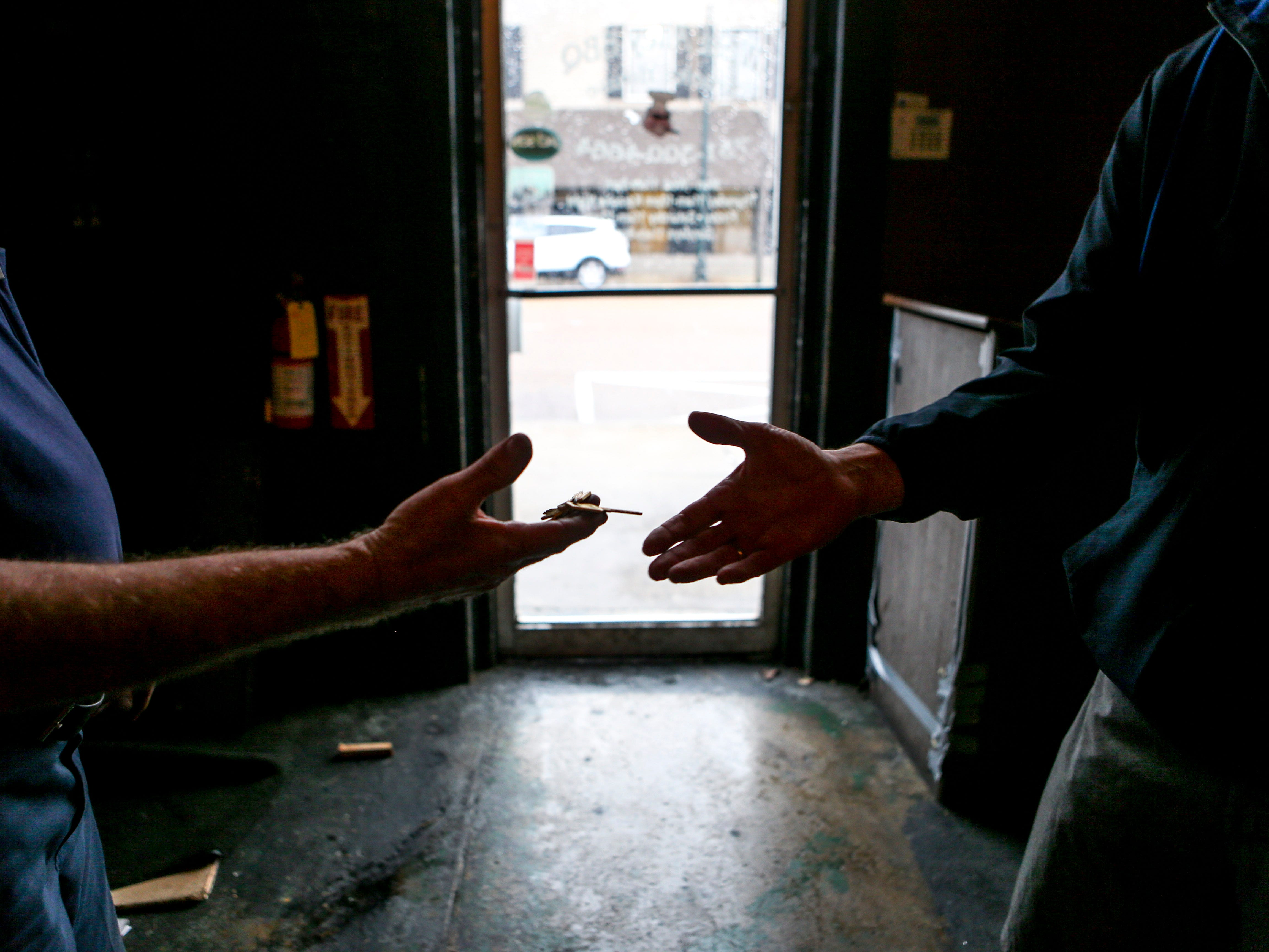 Steve Mooney, left, hands over newly crafted keys to Drew Baker, right, the new owner of the previous location of West Alley BBQ in Jackson, Tenn., on Friday, Nov. 30, 2018.