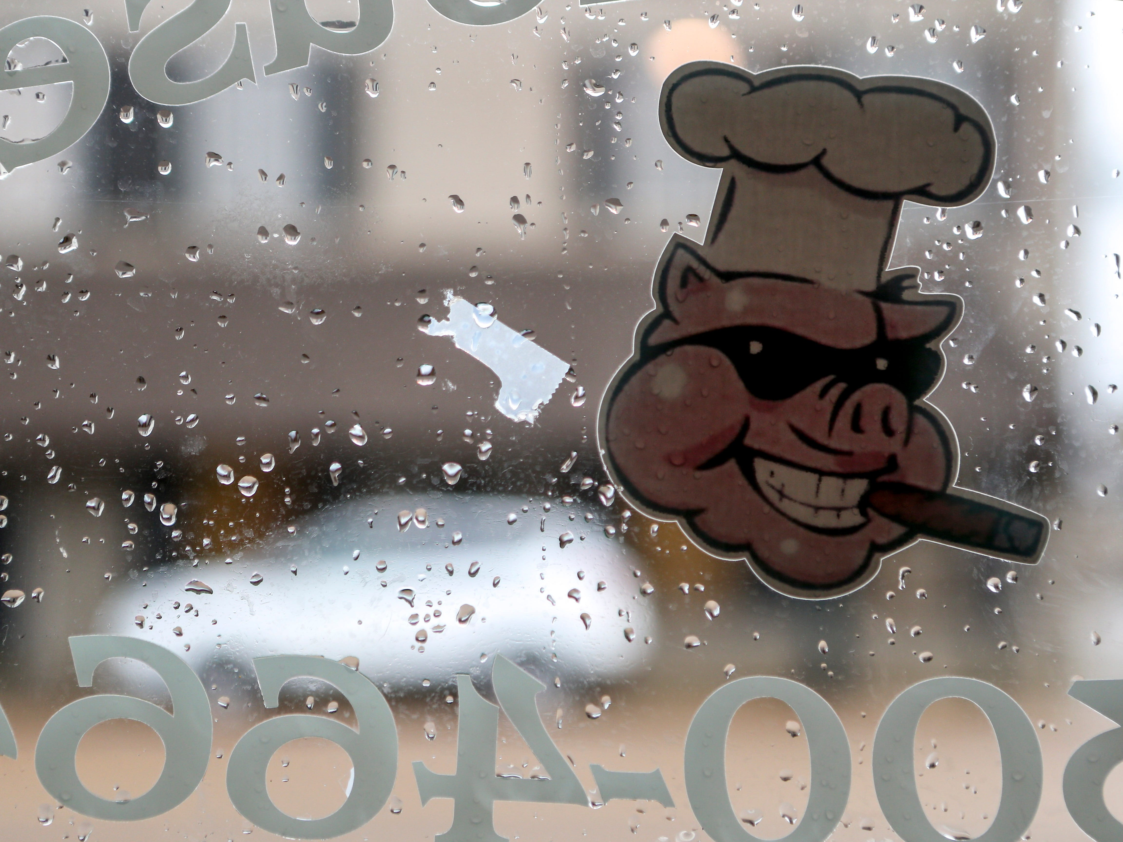 Rain drops dot the glass door on the day everything is cleared out in way of it's new owners at West Alley BBQ in Jackson, Tenn., on Friday, Nov. 30, 2018.