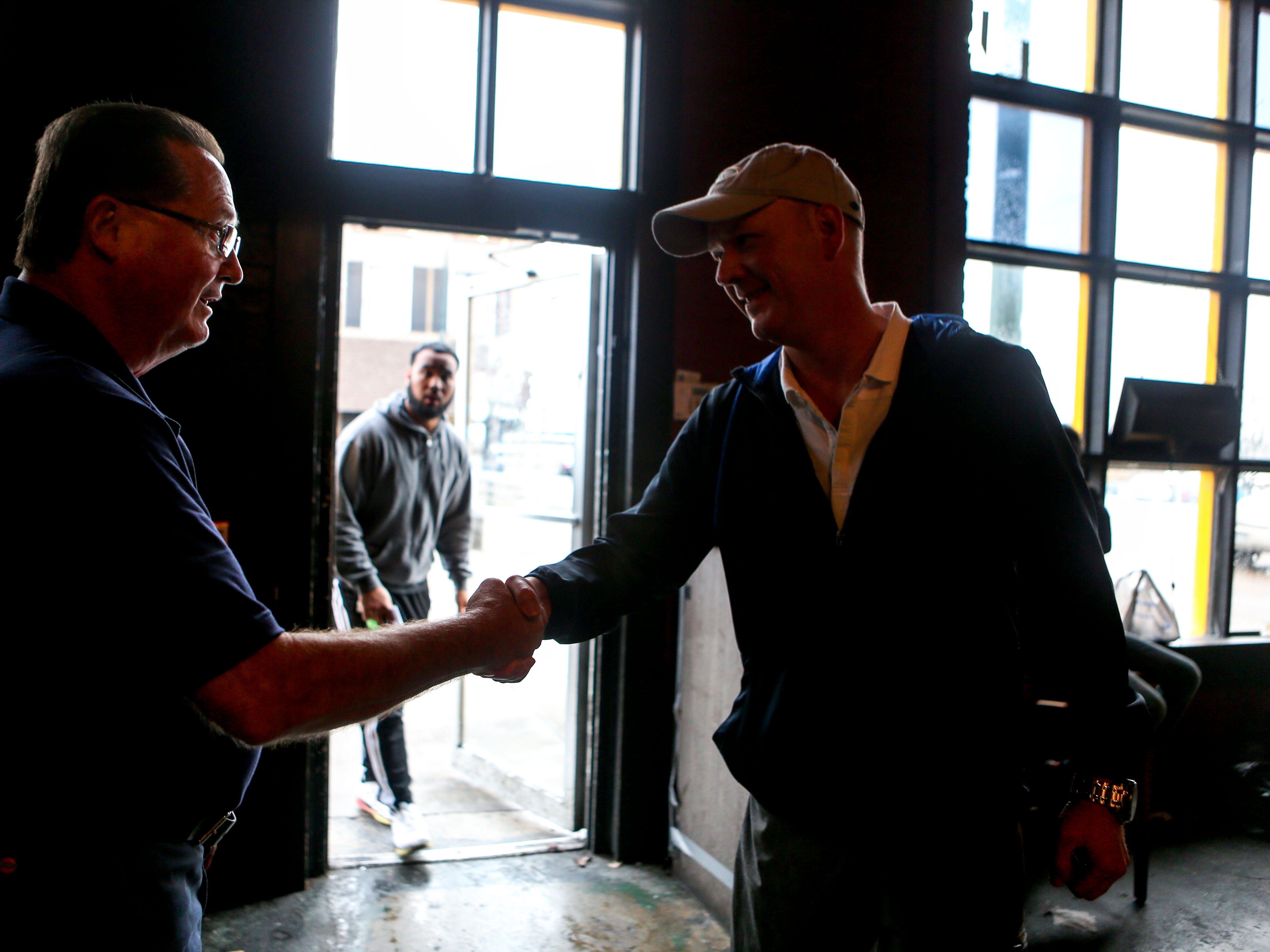 Steve Mooney, left, and Drew Baker, right, shake hands after Mooney presented Baker with a new set of keys for the location that previously housed West Alley BBQ in Jackson, Tenn., on Friday, Nov. 30, 2018.