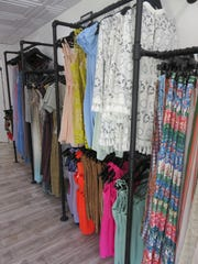 The Fancy Rascal's clothes representing multiple brands and designers hang on some racks designed by Jill Dyer.