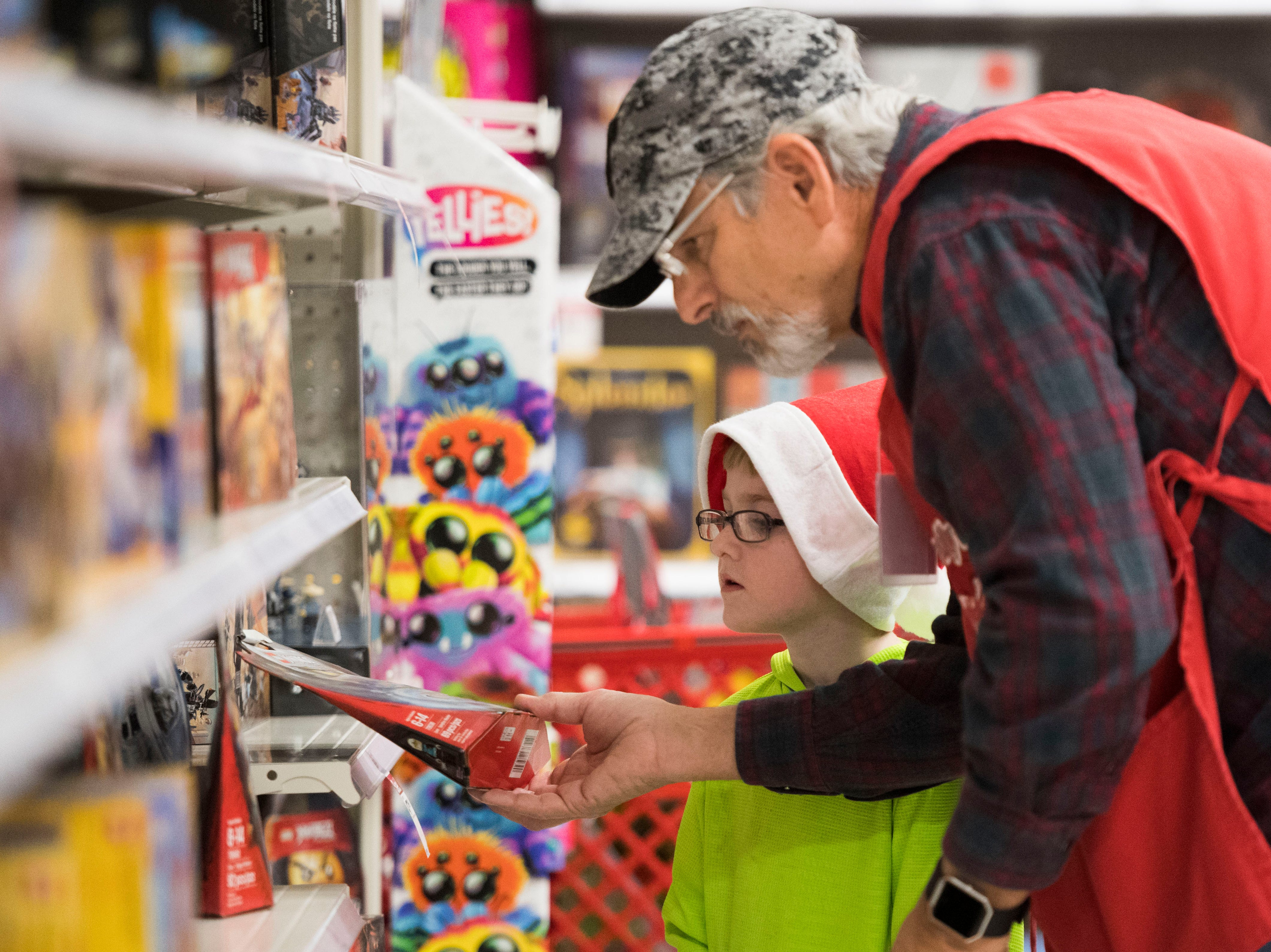 Brad Lofland helps Cason, 6, pick out a toy at the Target on Clinton Highway during the annual Weigel's Family Christmas Saturday, Dec. 1, 2018. This is the 21st year Weigel's has held the shopping spree for local underprivileged children.