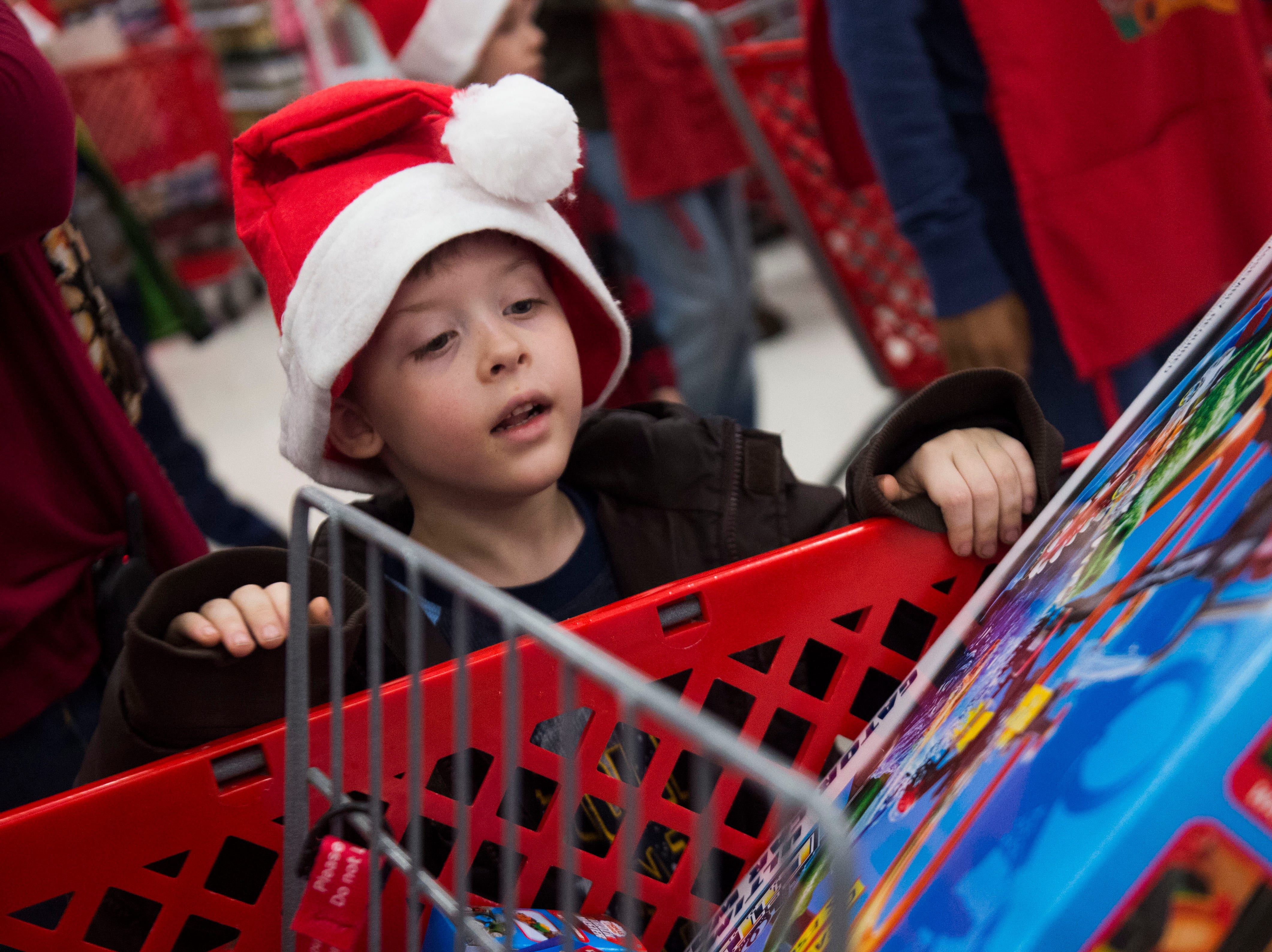 Children and their volunteers shop at the Target on Clinton Highway during the annual Weigel's Family Christmas Saturday, Dec. 1, 2018. This is the 21st year Weigel's has held the shopping spree for local underprivileged children.