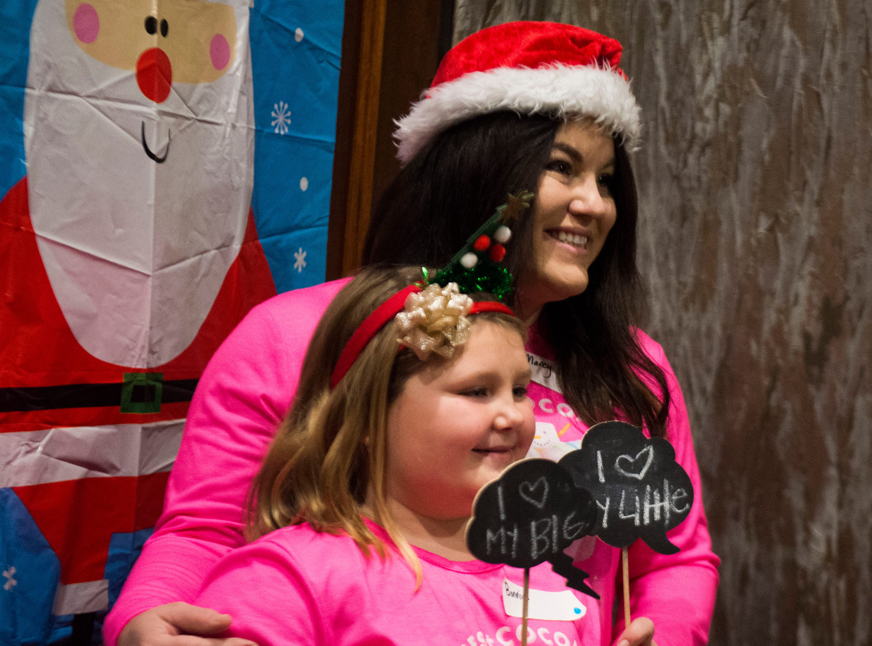 Big Marcy Ratcliff, and little Bonnie Huskey, 7,  pose for a photo at the Crowne Plaza for Big Brothers Big Sisters annual holiday party Saturday, Dec. 1, 2018. Nearly 300 mentors, mentees and family members were in attendance.