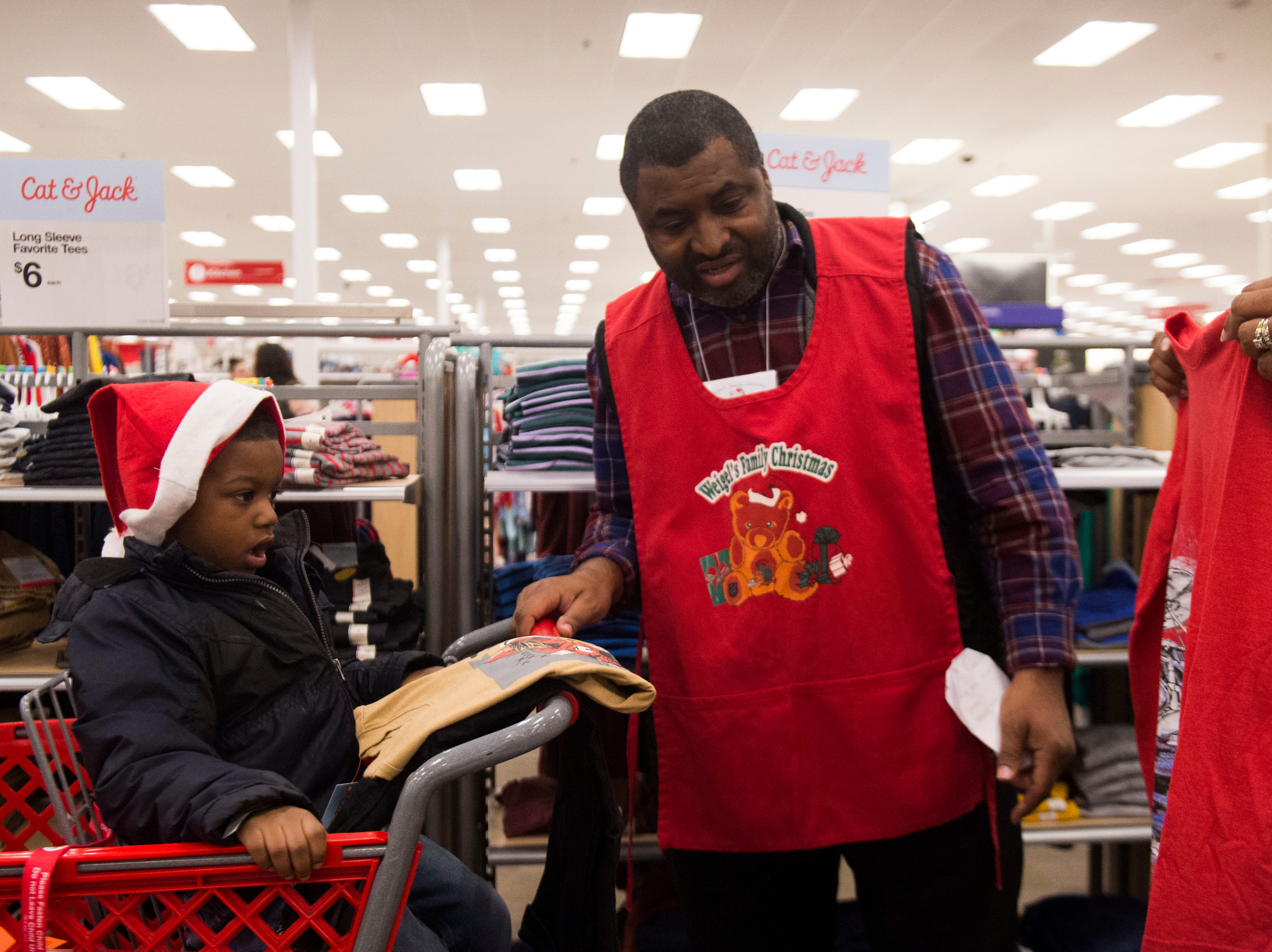Tara and Tim Spikes shop with Bakari, 4, at the Target on Clinton Highway during the annual Weigel's Family Christmas Saturday, Dec. 1, 2018. This is the 21st year Weigel's has held the shopping spree for local underprivileged children.