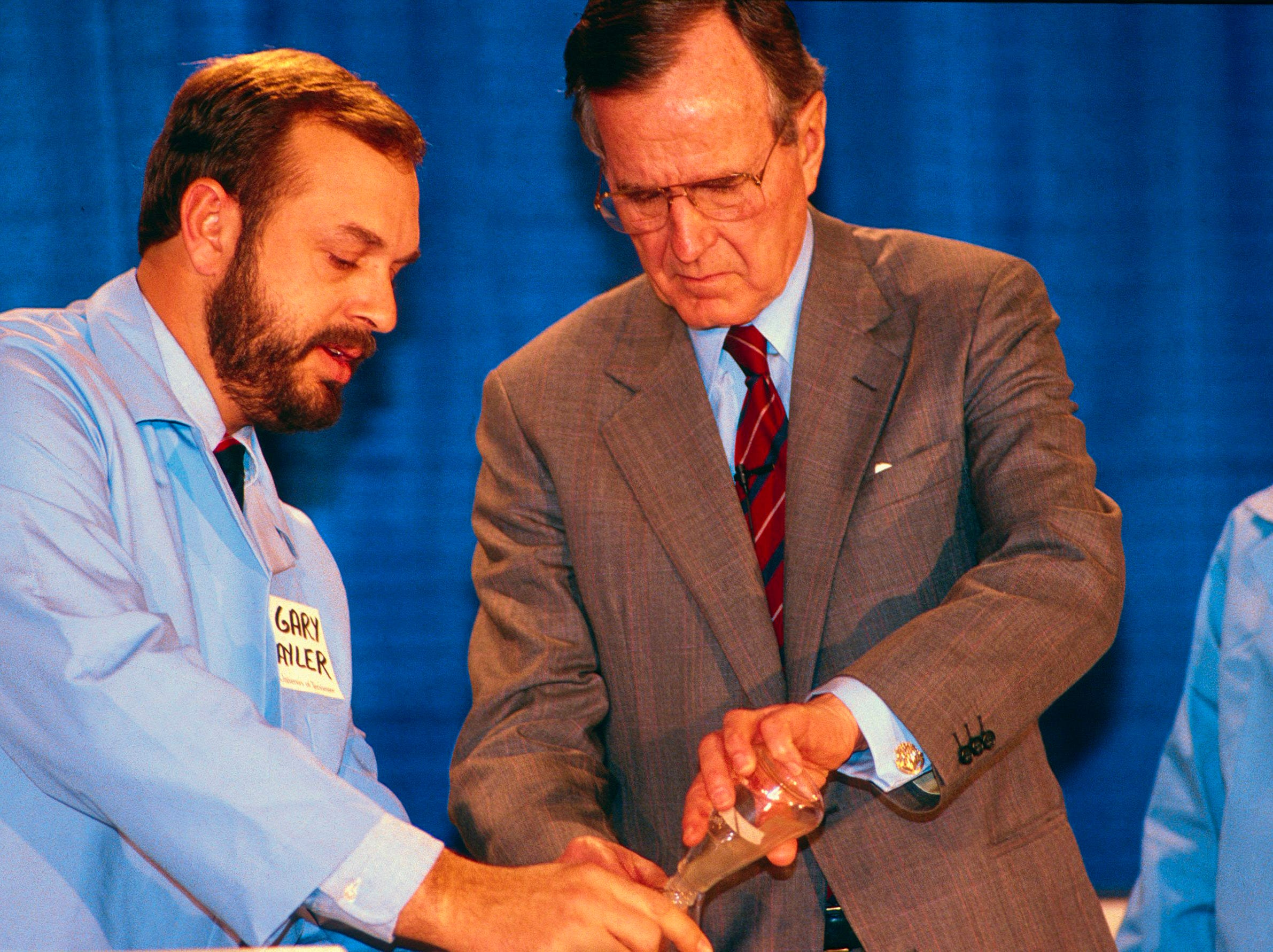 """Dr. Gary Sayler, left, and President George H.W. Bush perform an experiment for the cameras on Feb. 2, 1990, at the University of Tennessee. Sayler, director of the UT Center for Environmental Biotechnology, was demonstrating how bacteria can be used to """"eat,"""" or metabolize toxic waste."""